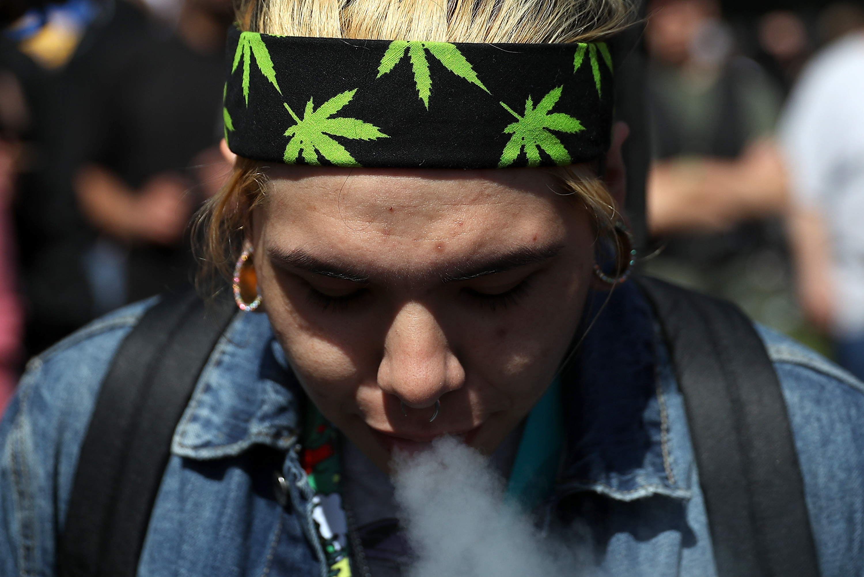 A marijuana user blows smoke after taking a hit from a bong during a 420 Day celebration on 'Hippie Hill' in Golden Gate Park on April 20, 2018, in San Francisco, California. (Getty)