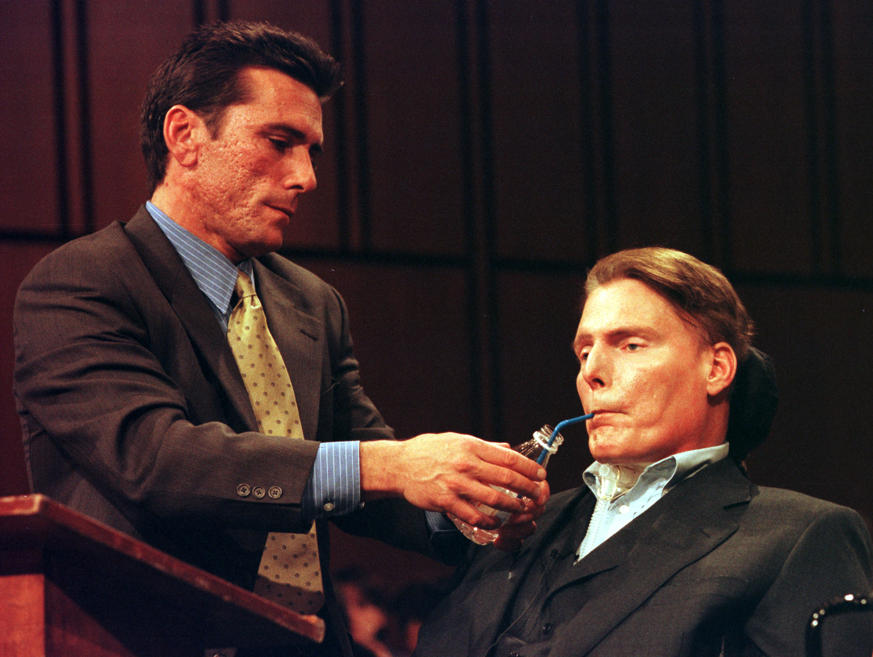 Actor Christopher Reeve is assisted as he testifies during a hearing on stem cell research April 26, 2000, on Capitol Hill in Washington, DC. (Getty)