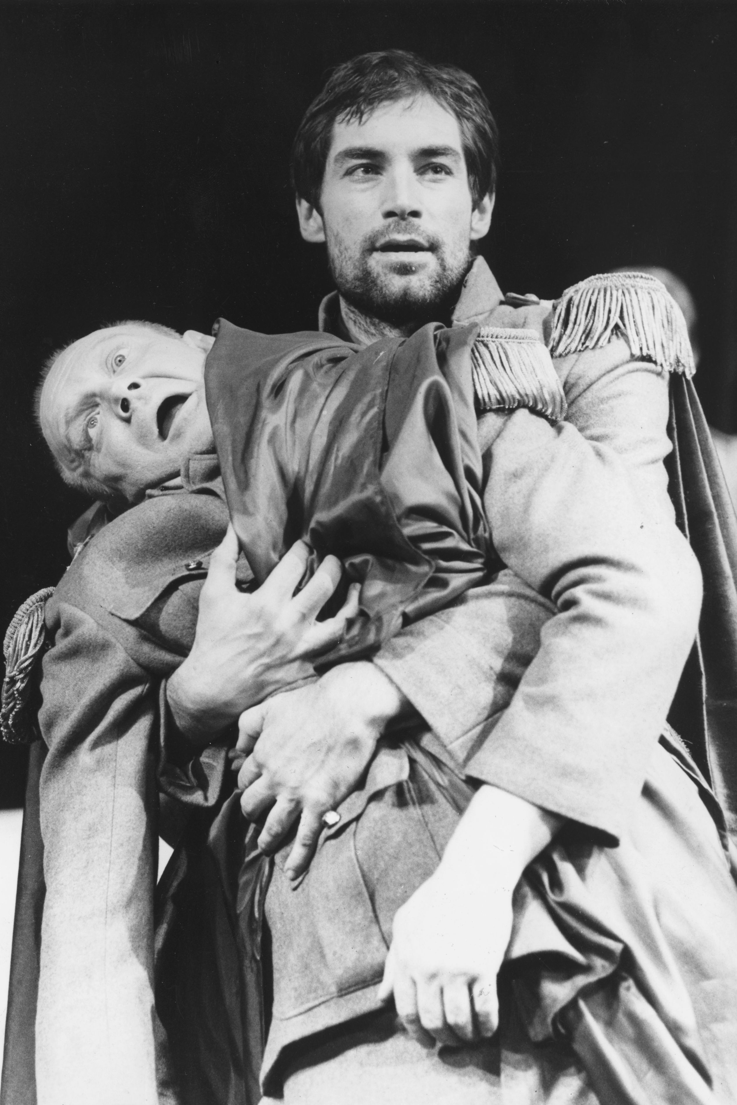 Julius Caesar (played by Morgan Sheppard) slumps dying in the arms of Antony (played by Timothy Dalton) during a performance of 'Shakespeare's Rome' at the Mermaid Theatre, London. (Source: Getty images)