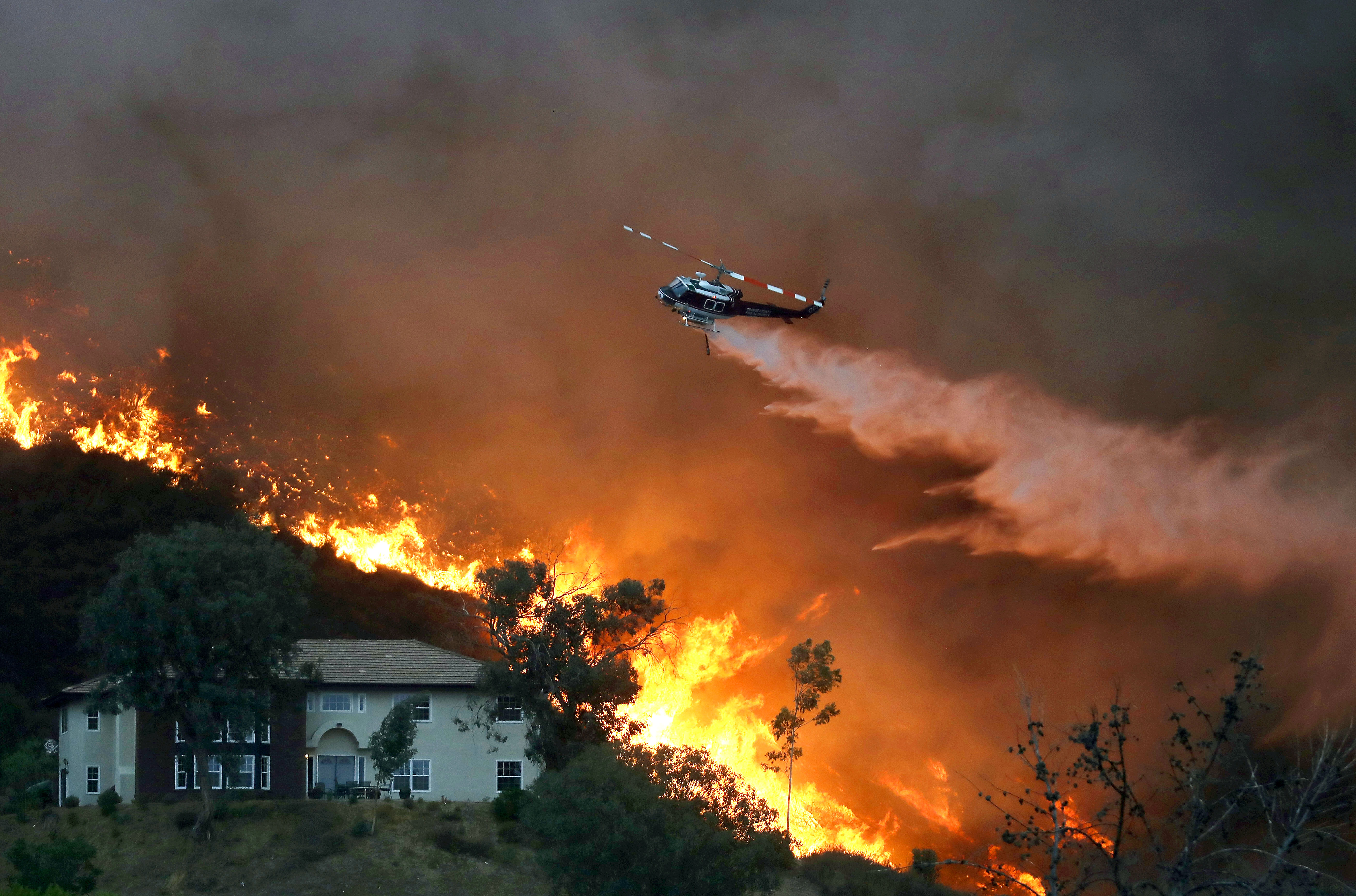 A firefighting helicopter makes a water drop as the Holy Fire burns near homes on August 9, 2018 in Lake Elsinore, California. The fire continues to grow amidst a heat wave and has now burned 10,236 acres while remaining just five percent contained.