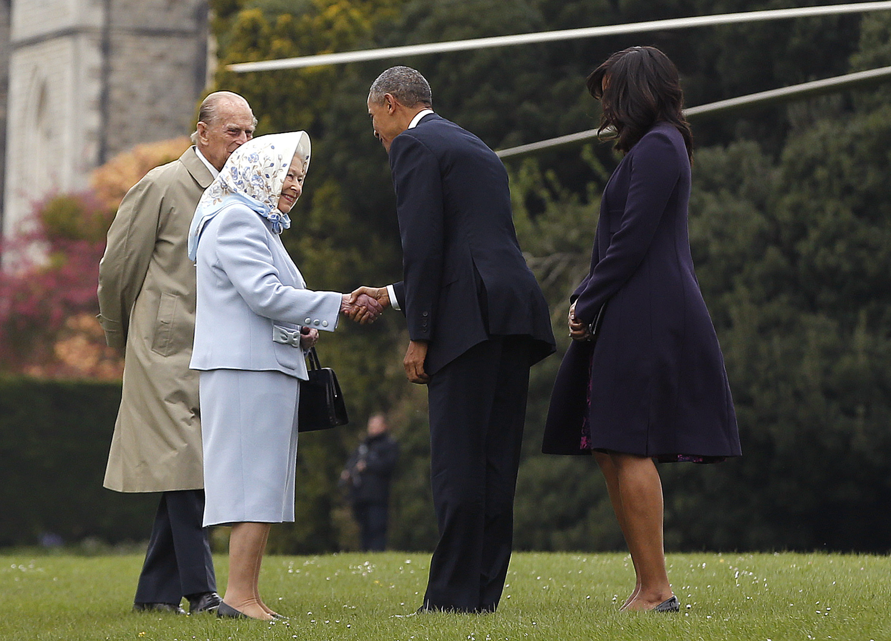 US President Barack Obama and his wife First Lady Michelle Obama are greeted by Queen Elizabeth II and Prince Phillip, Duke of Edinburgh after landing by helicopter at Windsor Castle for a private lunch on April 22, 2016.