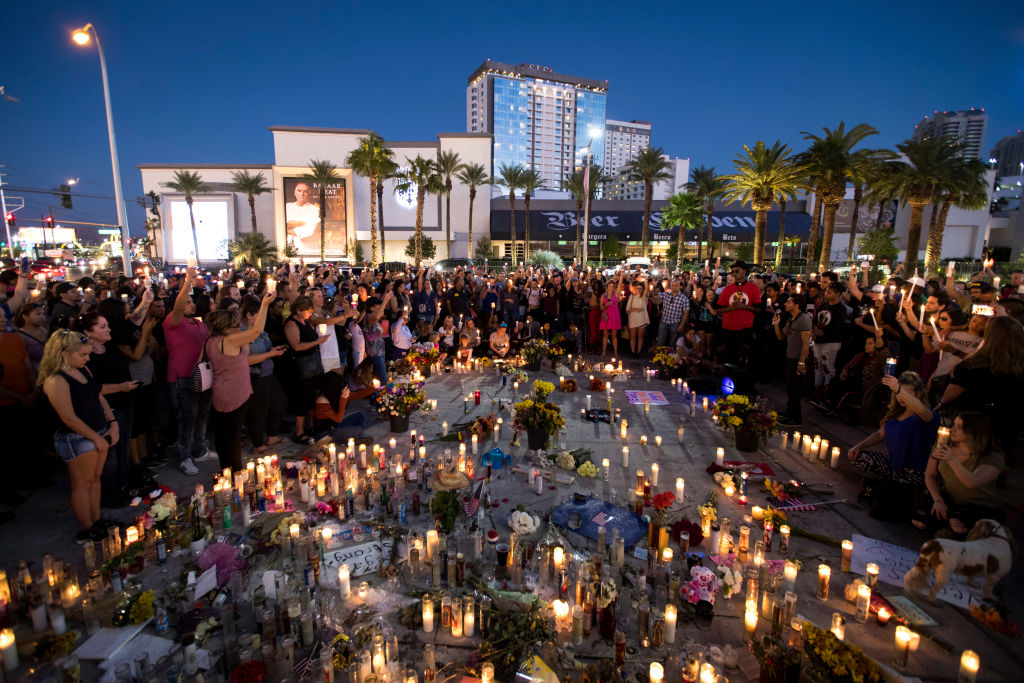Mourners hold their candles in the air during a moment of silence during a vigil to mark one week since the mass shooting at the Route 91 Harvest country music festival, on the corner of Sahara Avenue and Las Vegas Boulevard at the north end of the Las Vegas Strip, on October 8, 2017 in Las Vegas, Nevada.(Photo by Drew Angerer/Getty Images)
