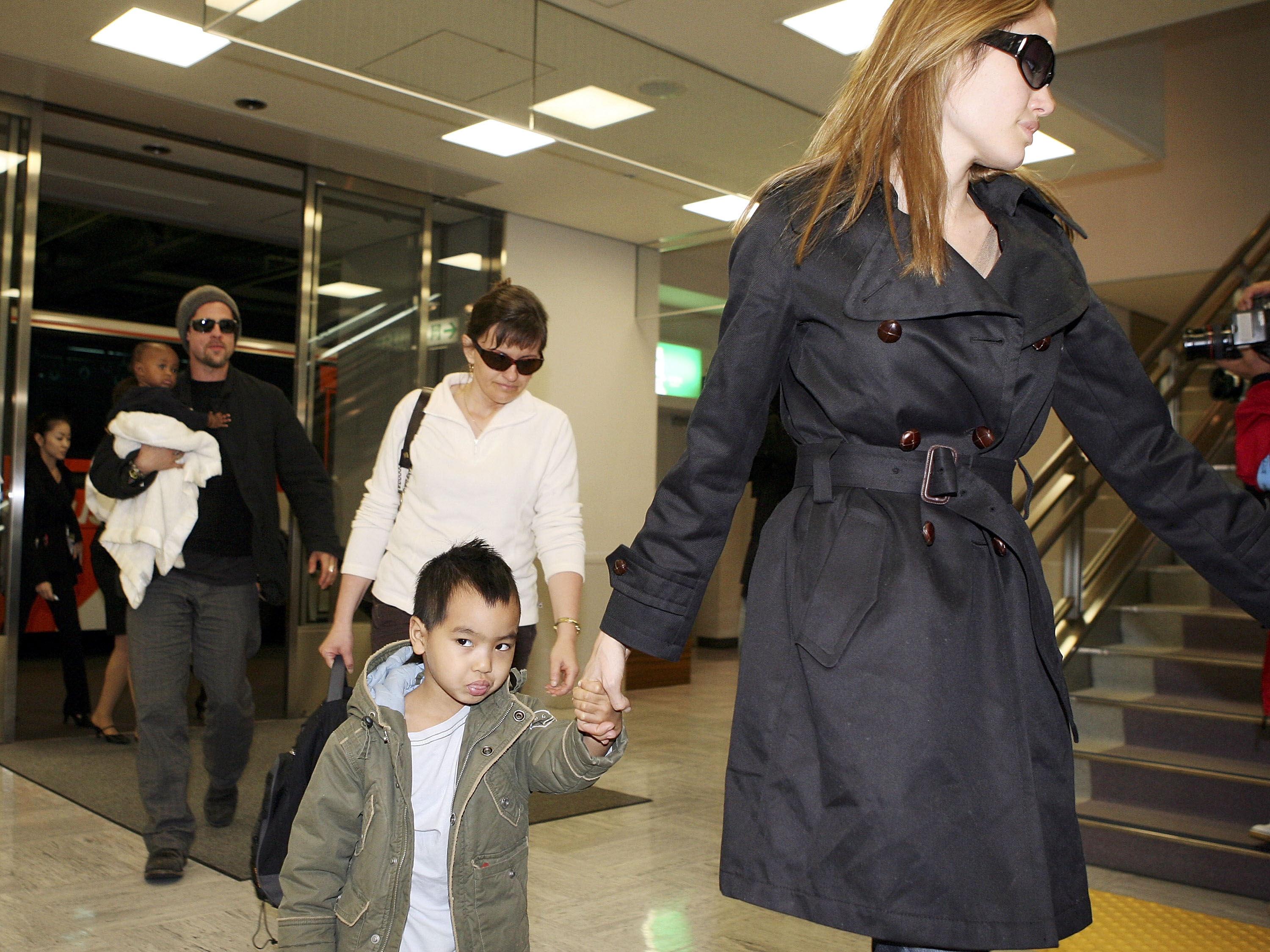 Actor Brad Pitt and actress Angelina Jolie arrive with Jolie's children Zahara Marley Jolie and Maddox Jolie at the New Tokyo International Airport on November 27, 2005, in Narita, Japan. Pitt and Jolie are in Japan to promote a film 'Mr. and Mrs. Smith.' (Getty Images)