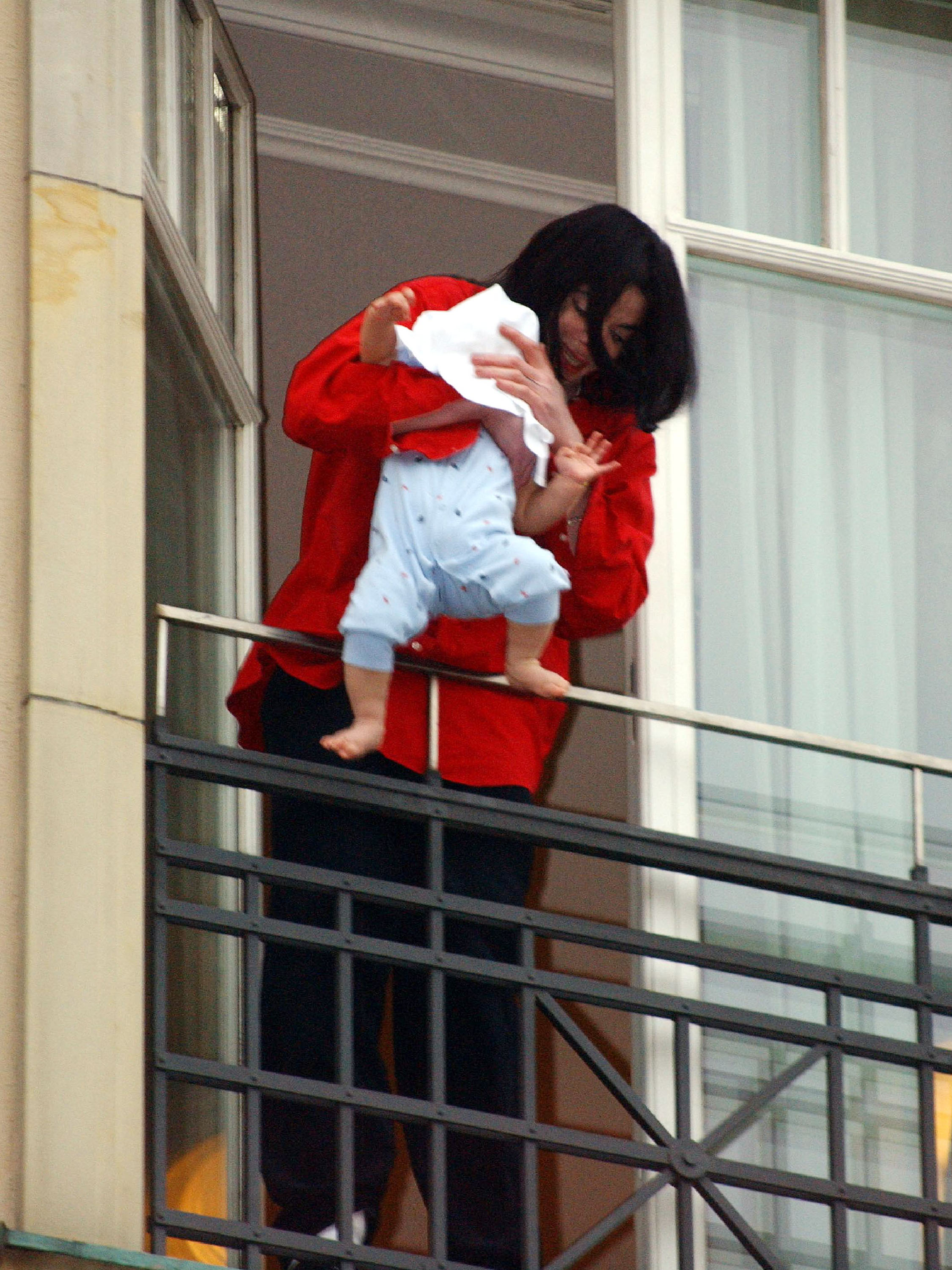 Singer Michael Jackson holds his eight-month-old son Prince Michael II over the balcony of the Adlon Hotel November 19, 2002 in Berlin, Germany. (Photo by Olaf Selchow/Getty Images)