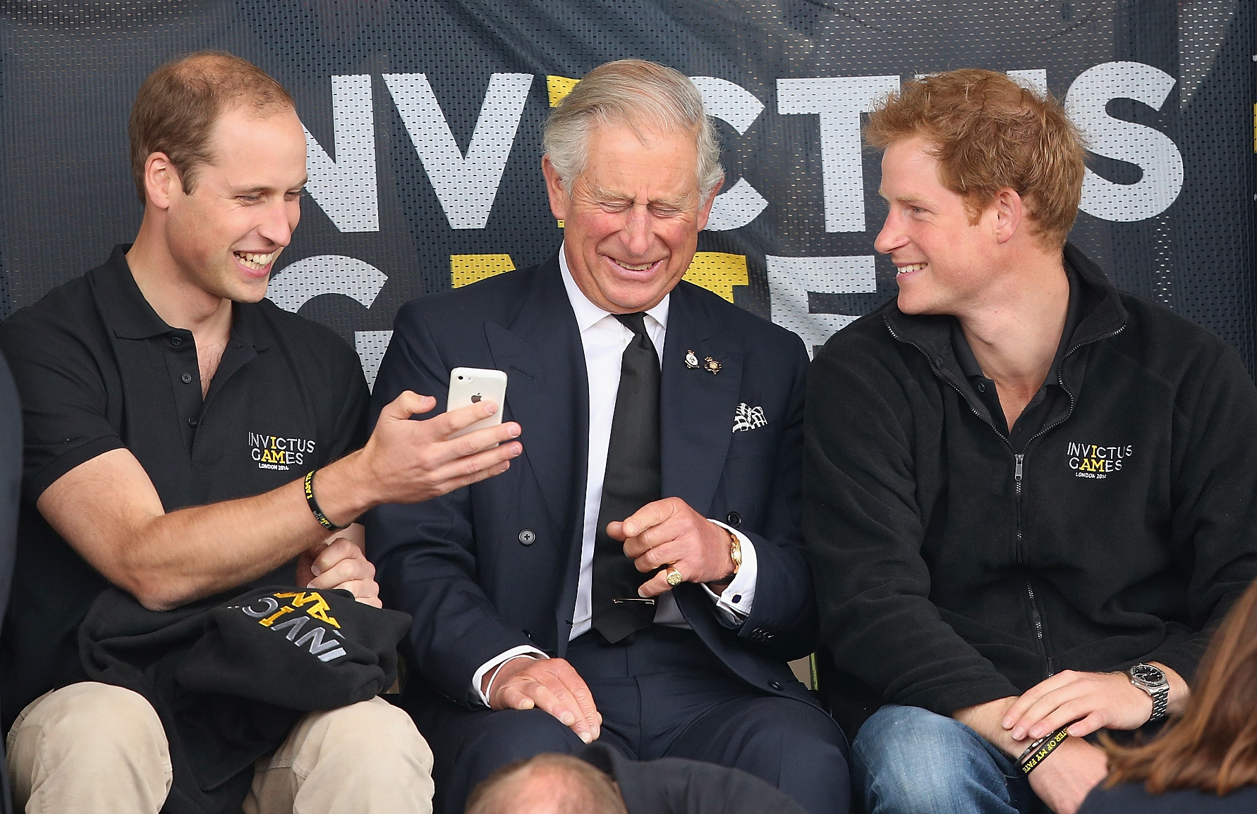 Prince William, Duke of Cambridge, Prince Harry and Prince Charles, Prince of Wales look at a mobile phone as they watch the athletics at Lee Valley Track during the Invictus Games on September 11, 2014 in London, England. (Photo by Chris Jackson/Getty Images)