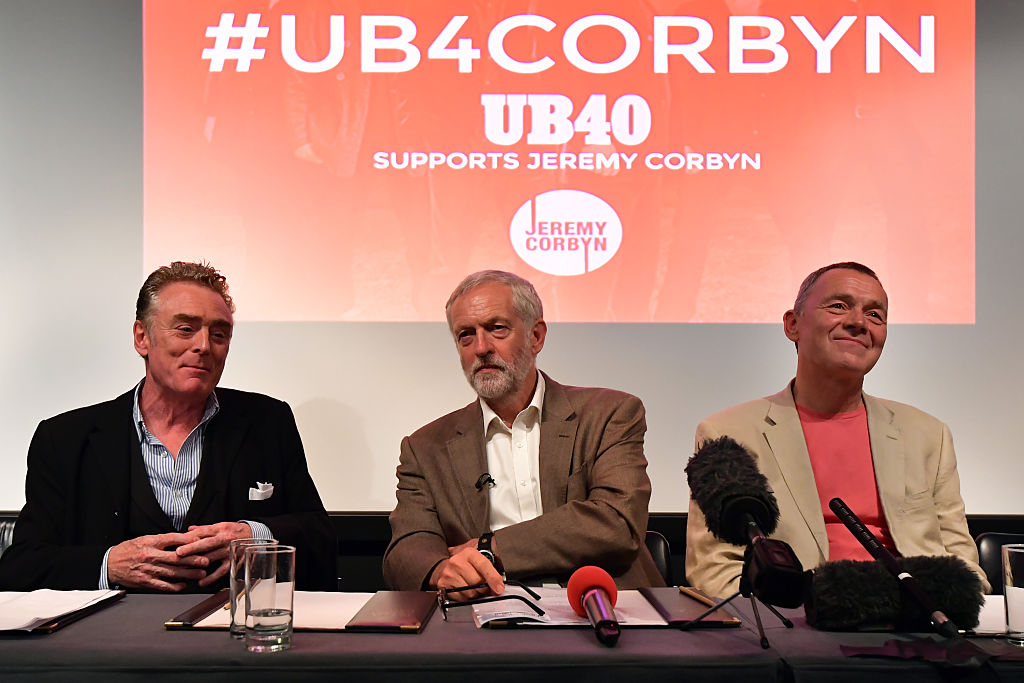 Jeremy Corbyn (C) sits with members of UB40 Brian Travers (L) and Duncan Campbell (R) during a joint press conference in which the reggae band announced their support for the party leader, on September 6, 2016 in London, England. (Photo by Carl Court/Getty Images)