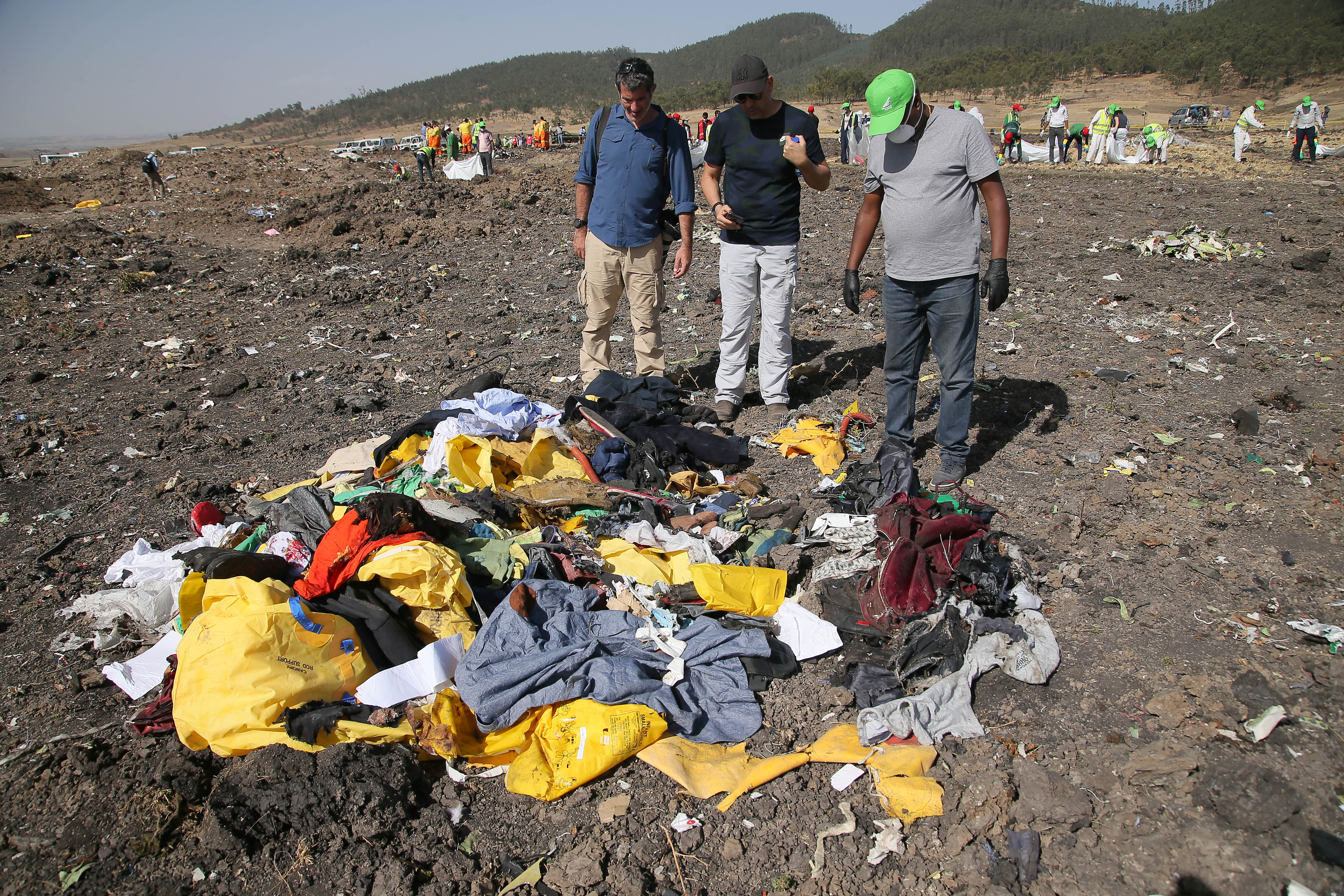 A man searching for personal effects belonging to his brother (center) who was a passenger on ET 302 speaks to a journalist and Recovery worker at the crash site of Ethiopian Airlines Flight ET 302 on March 12, 2019, in Bishoftu, Ethiopia. (Getty)