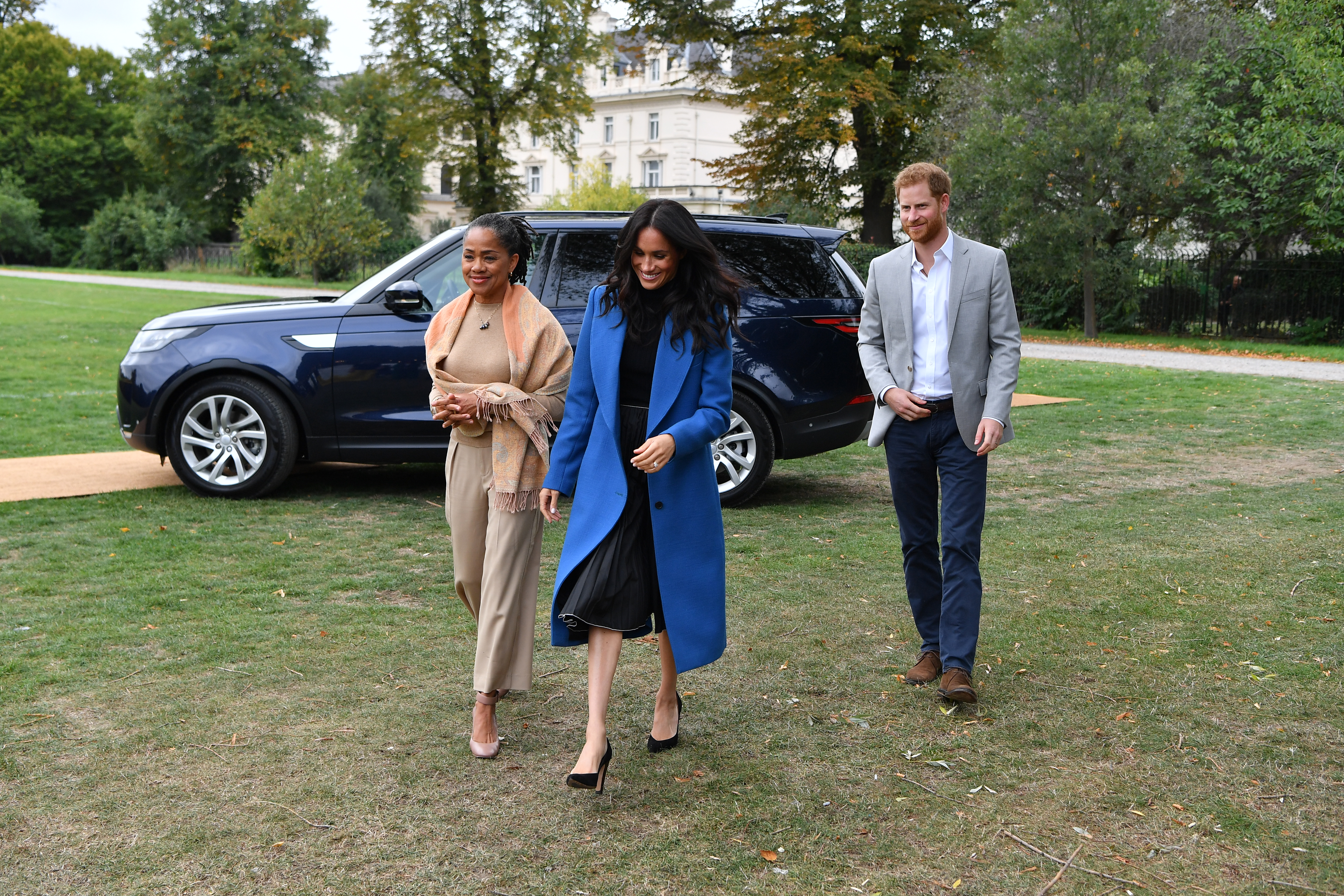 Meghan, Duchess of Sussex (C) arrives with her mother Doria Ragland (L) and Prince Harry, Duke of Sussex to host an event to mark the launch of a cookbook with recipes from a group of women affected by the Grenfell Tower fire at Kensington Palace on September 20, 2018 in London, England.