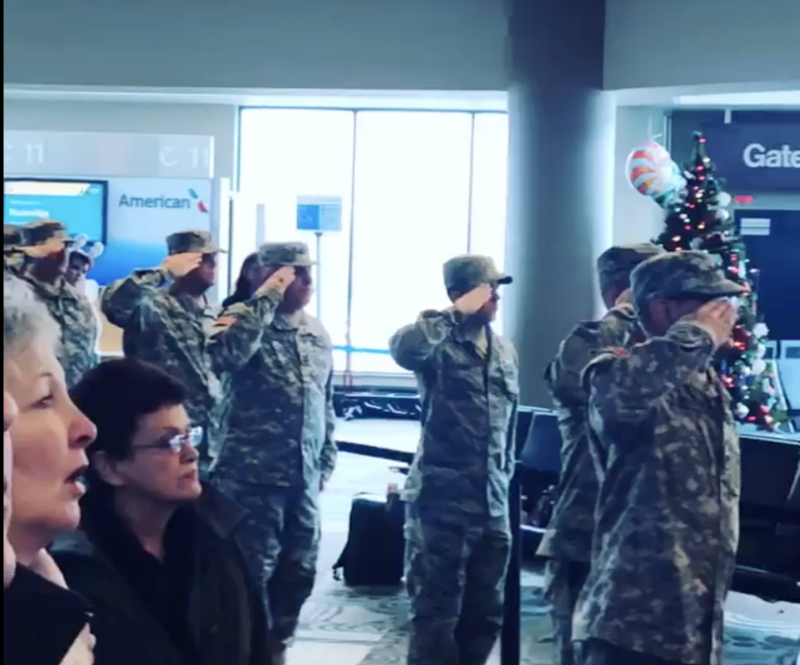 Active servicemen and women stand in attention and salute while travelers sing the national anthem (Source: Facebook)