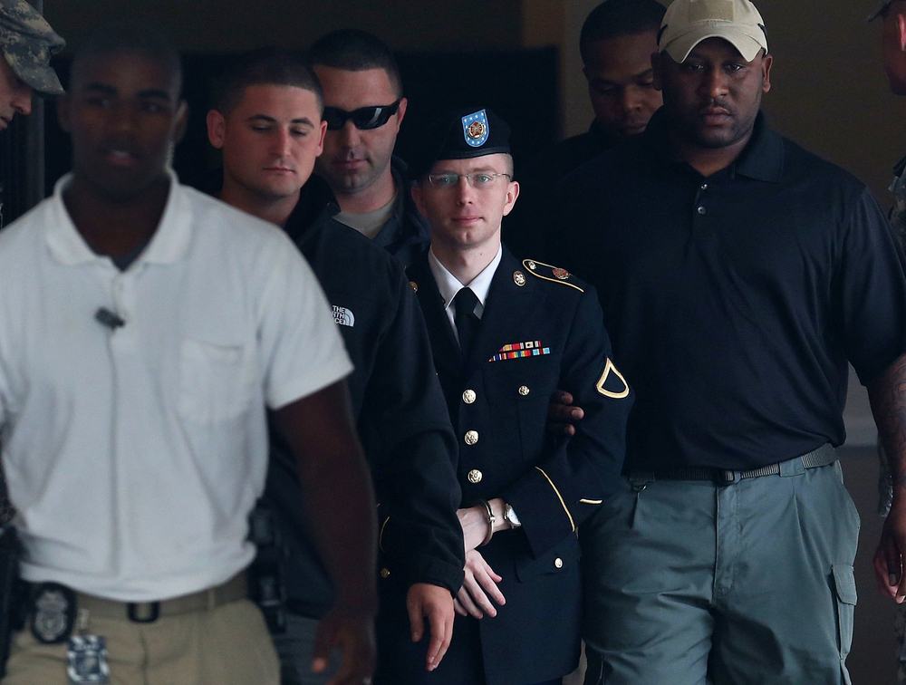 US Army Private First Class Bradley Manning is escorted out of a military court facility during the sentencing phase of his trial August 20, 2013, in Fort Meade, Maryland. Manning was found guilty of several counts under the Espionage Act but acquitted of the most serious charge of aiding the enemy. (Photo by Mark Wilson/Getty Images)