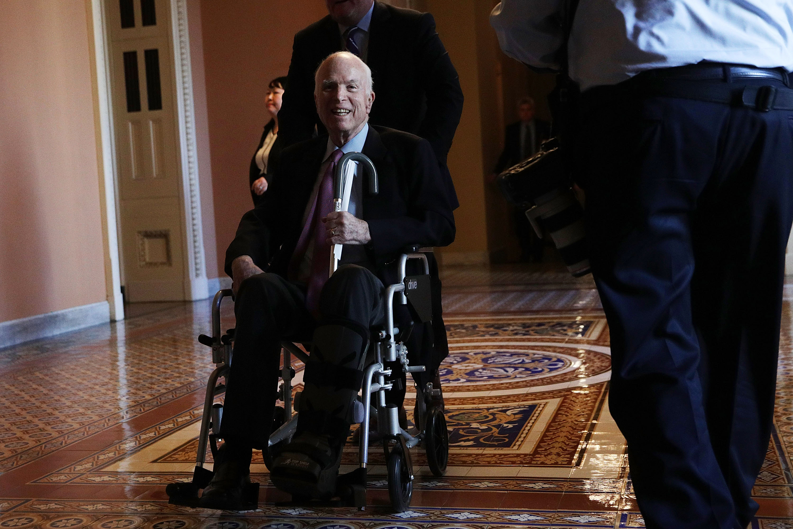 U.S. Sen. John McCain (R-AZ) passes by on a wheelchair in a hallway at the Capitol December 1, 2017 in Washington, DC. Senate GOPs indicate that they have enough votes to pass the tax reform bill. (Getty Images)