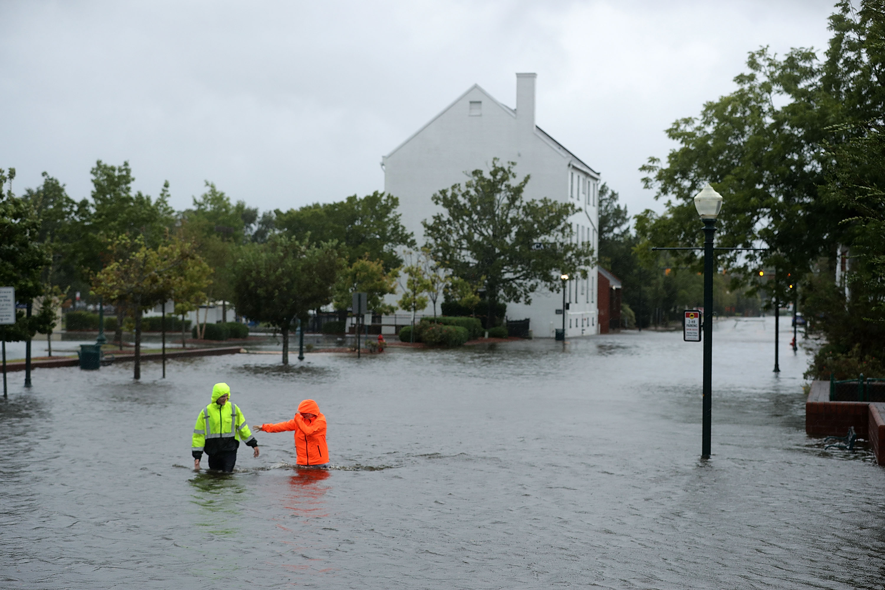 Residents walk in flooded streets as the Neuse River floods its banks during Hurricane Florence September 13, 2018 in New Bern, North Carolina. Coastal cities in North Carolina, South Carolina and Virginia are under evacuation orders as the Category 2 hurricane approaches the United States.