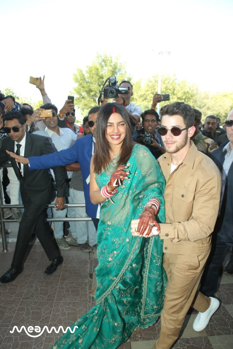 Both Priyanka and Nick looked completely besotted wth each other as they held hand and posed for pictures outside the Jodhpur airport terminal. (Meaww Photos)
