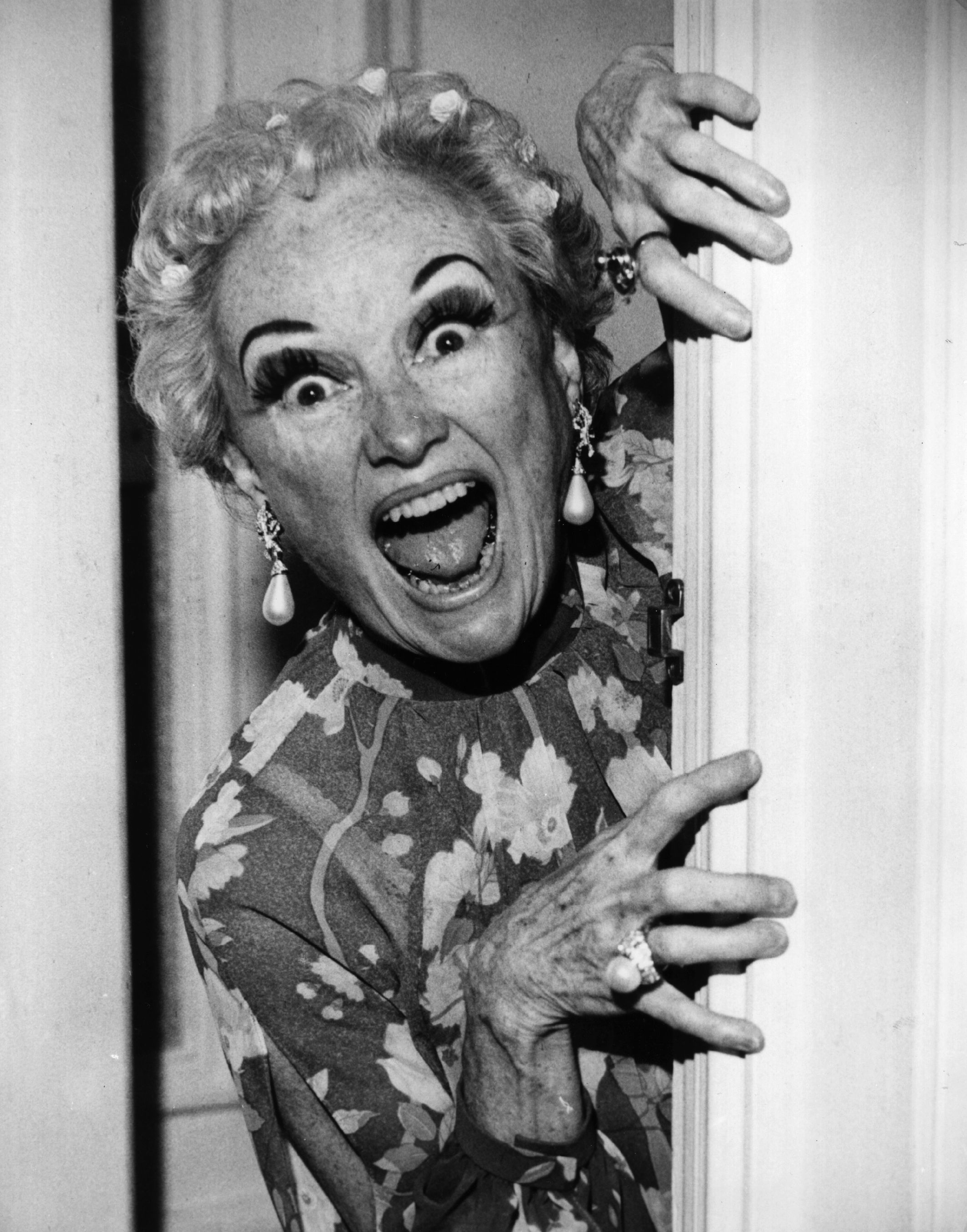 Hollywood comedienne Phyllis Diller playing peek-a-boo with the cameraman before the start of her television show 'Bonkers'.