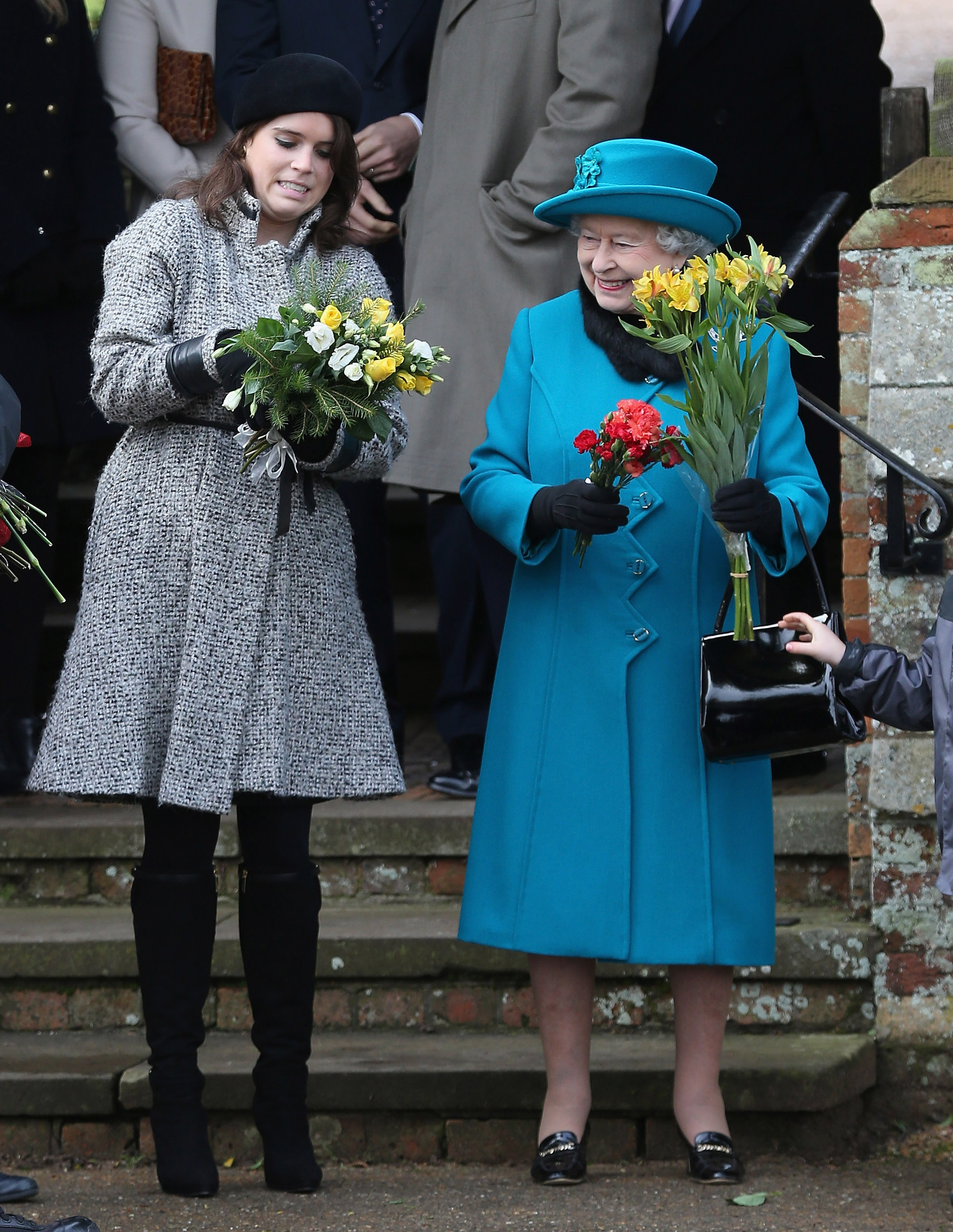 Queen Elizabeth II hands flowers to Princess Eugenie as they leave St Mary Magdalene Church after attending the traditional Christmas Day church service on December 25, 2012 in Sandringham, near King's Lynn, England.