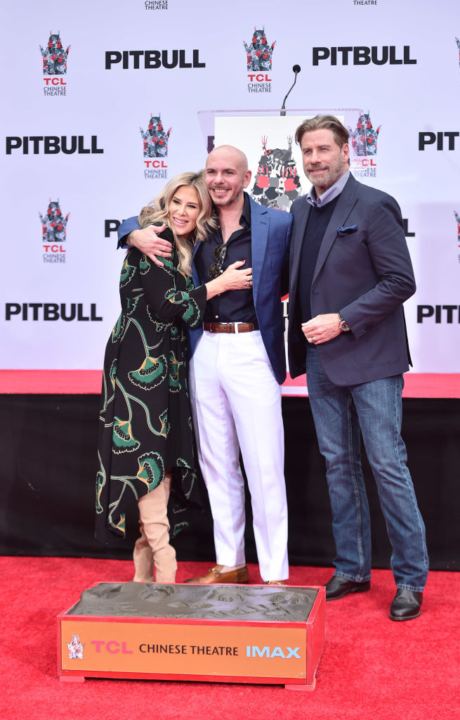 Ellen K, Pitbull and John Travolta attend the Hand And Footprint Ceremony Honoring Pitbull at TCL Chinese Theatre on December 14, 2018 in Hollywood, California (Photo by Alberto E. Rodriguez/Getty Images)