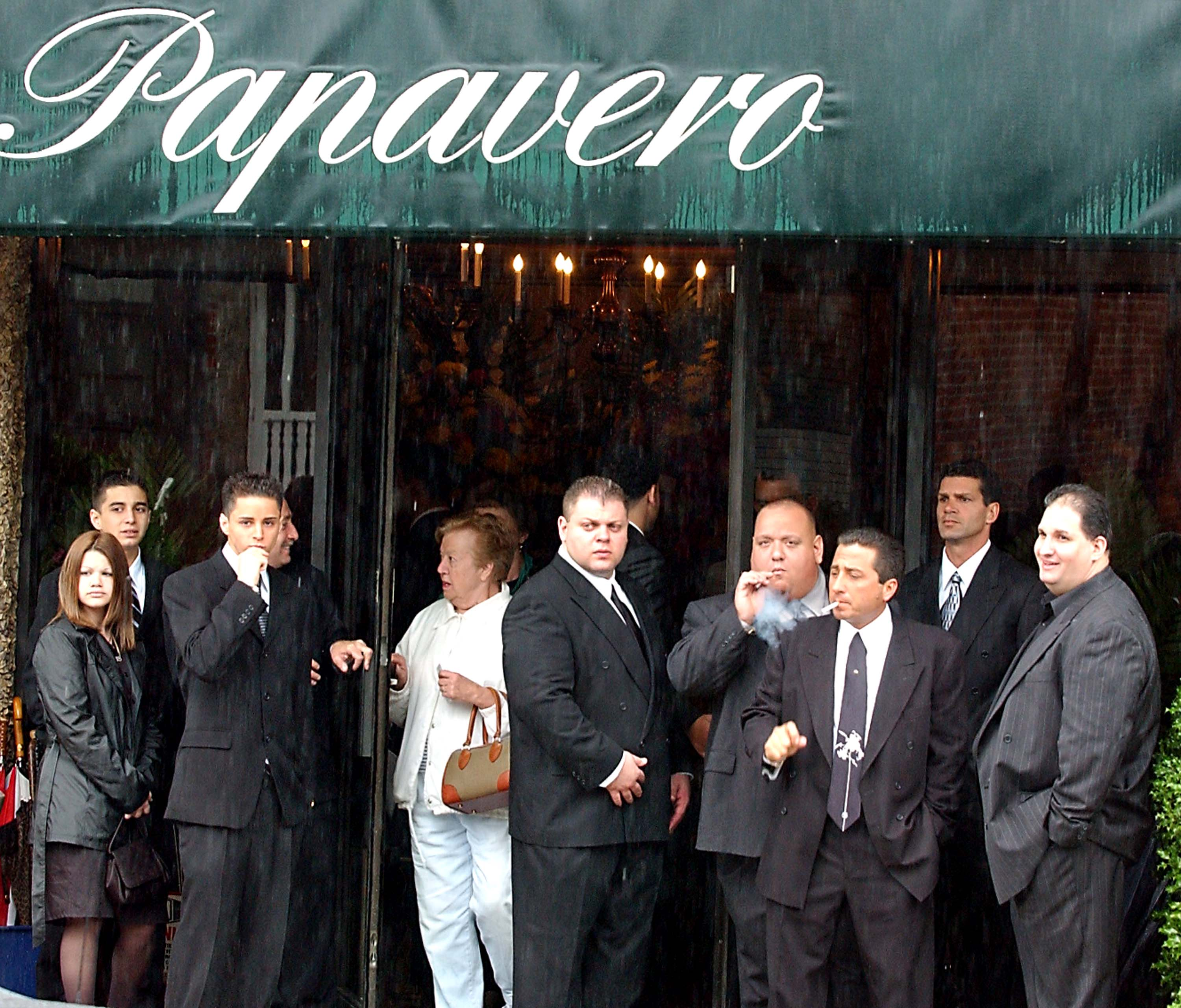Friends and family stand in front of the Papavero funeral home to attend the wake for mobster John Gotti, June 14, 2002 in the Queens borough of New York City. Gotti was interred in a crypt the following day at St John's Cemetery in Middle Village, Queens.