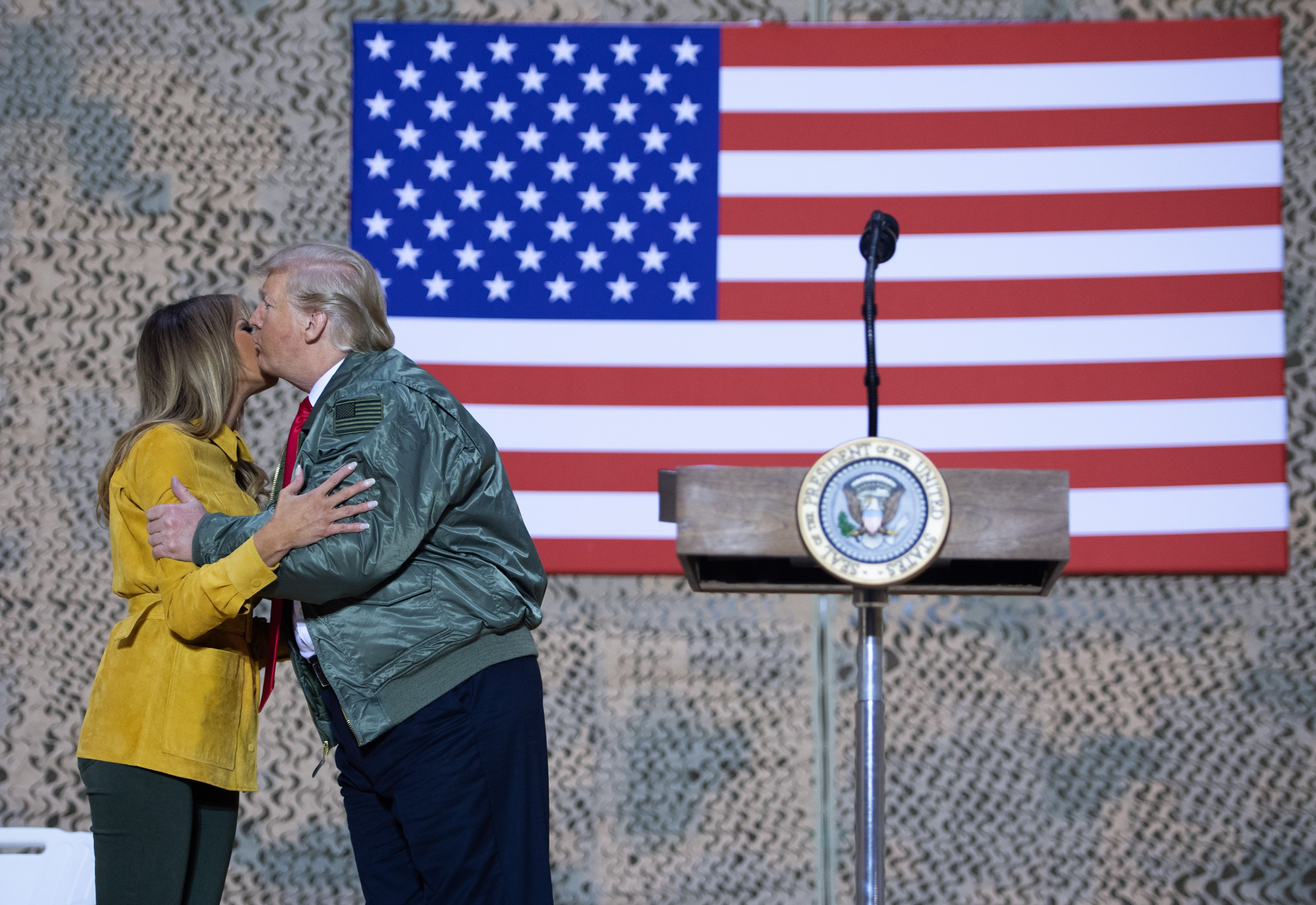 "As a part of their visit, the First Couple posed for photographs with US military personnel and treated the audience to a rare ""public display of affection"" while they were at it. (Source: Getty Images)"