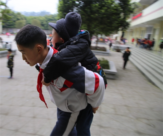 Come rain or shine, Xu Bingyang, 12, carries Zhang Ze to school every single day. (Sichuan Online)