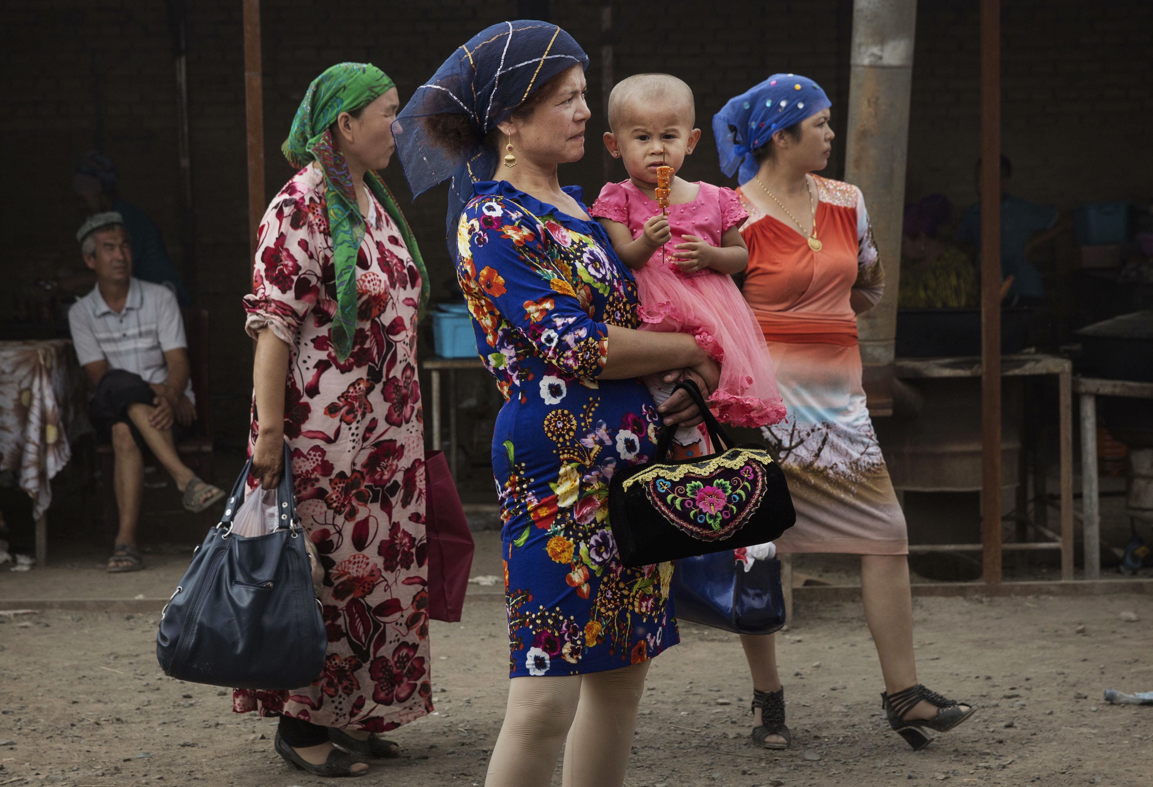 Uyghur women stand in a market while shopping before the Corban Festival on September 10, 2016 in Turpan County, in the far western Xinjiang province, China. (Getty Images)