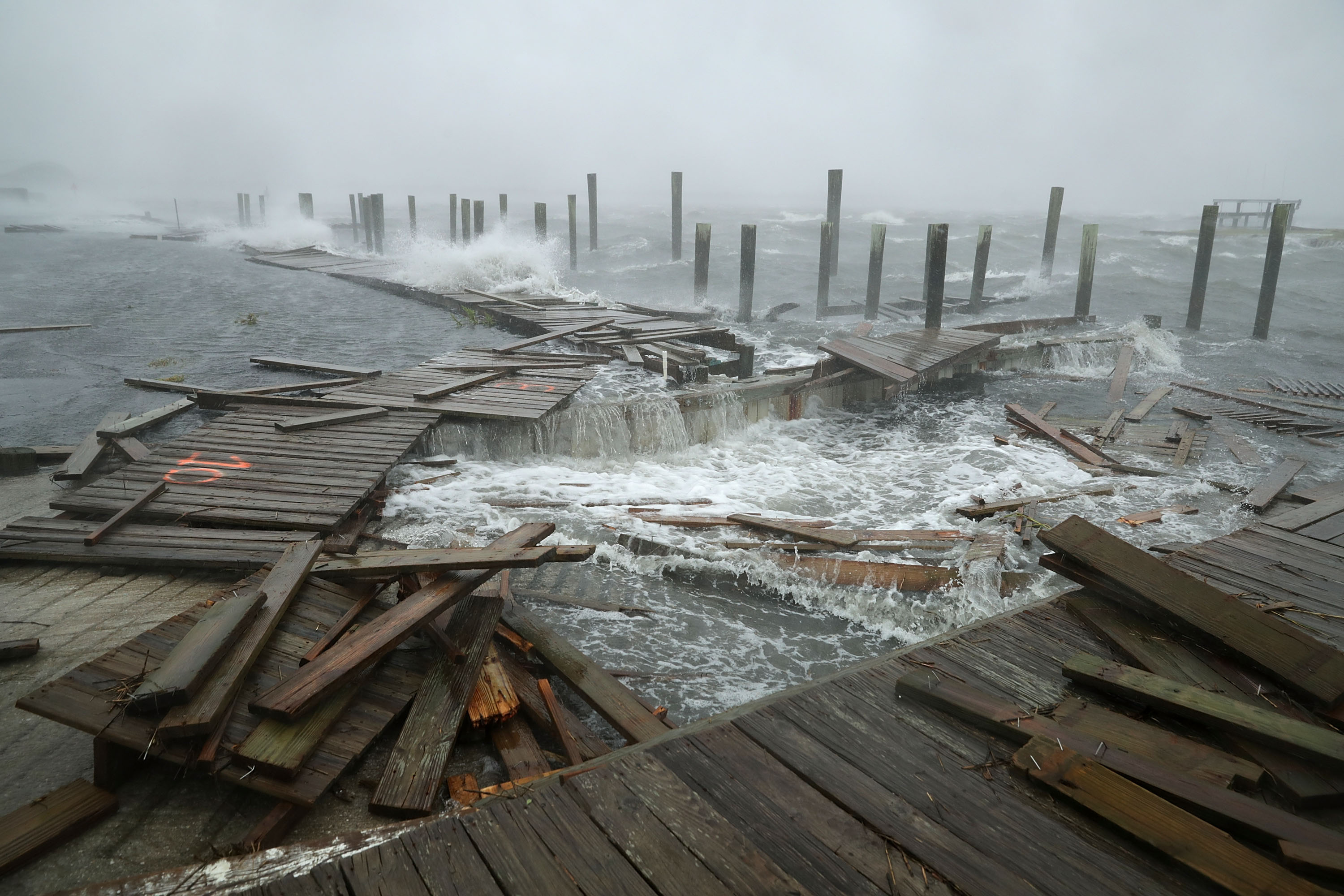 Portions of a boat dock and boardwalk are destroyed by powerful wind and waves as Hurricane Florence arrives September 13, 2018 in Atlantic Beach, United States. Coastal cities in North Carolina, South Carolina and Virginia are under evacuation orders as the Category 2 hurricane approaches the United States.