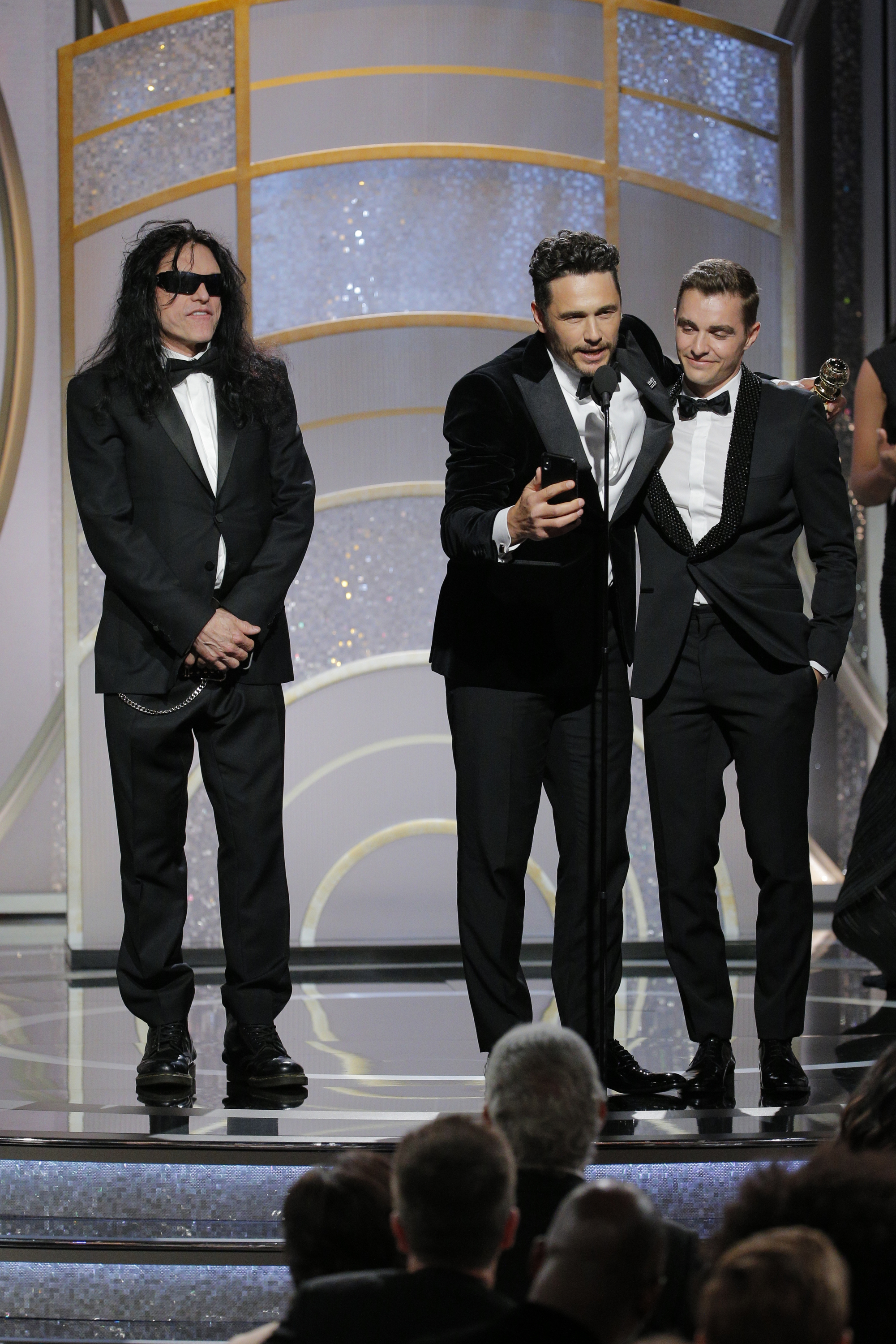 "In this handout photo provided by NBCUniversal, James Franco, with Tommy Wiseau and Dave Franco, accepts the award for Best Performance by an Actor in a Motion Picture – Musical or Comedy for ""The Disaster Artist"" during the 75th Annual Golden Globe Awards at The Beverly Hilton Hotel on January 7, 2018 in Beverly Hills, California."