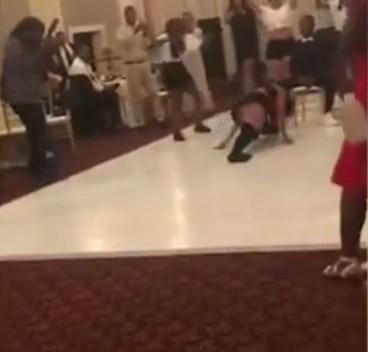 The bride, who walked down the aisle in a bedazzling golden gown, chose to undergo a very dramatic change in costume for her surprise twerk performance. (Source: YouTube)