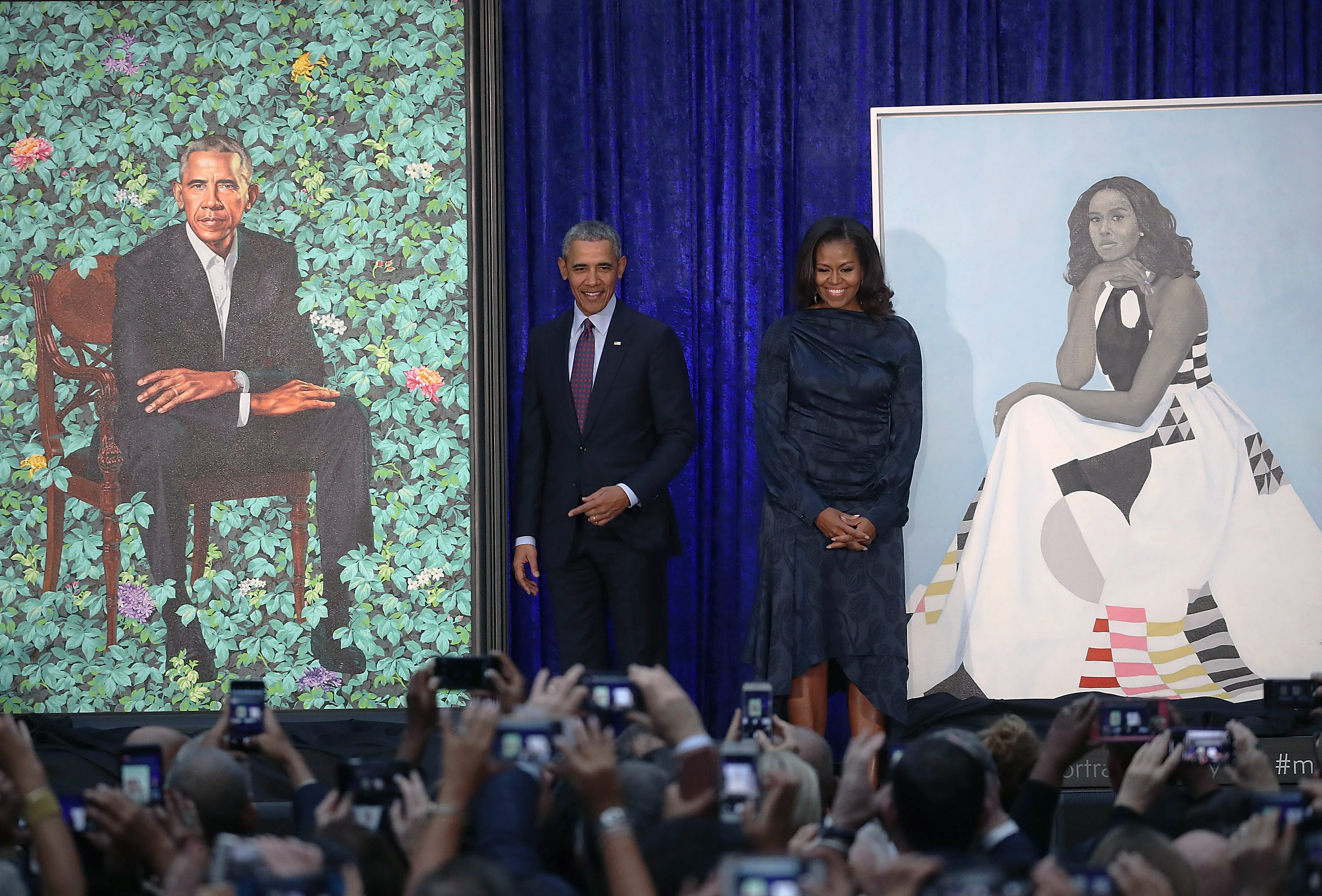 Former U.S. President Barack Obama and former first lady Michelle Obama stand next to their newly unveiled portraits during a ceremony at the Smithsonian's National Portrait Gallery, on February 12, 2018 in Washington, DC. The portraits were commissioned by the Gallery, for Kehinde Wiley to create President Obama's portrait, and Amy Sherald that of Michelle Obama (Getty Images)
