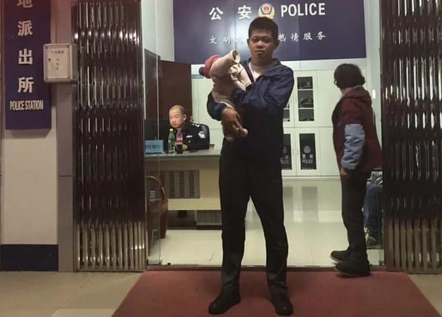 The father pictured with his newborn infant (Source: Yiwu Police)