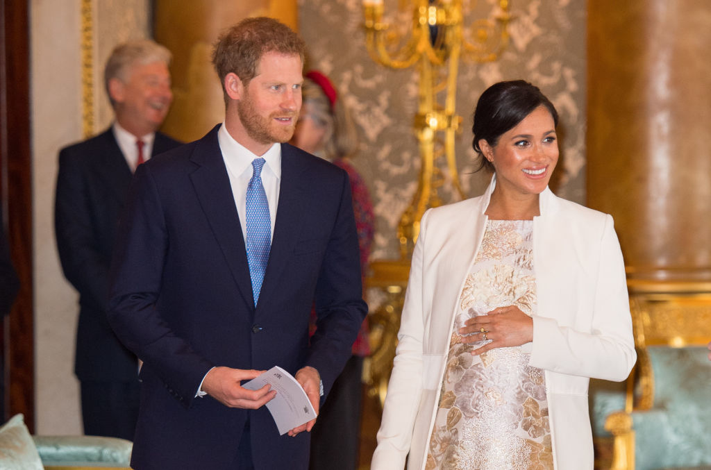 Meghan, Duchess of Sussex and Prince Harry, Duke of Sussex attend a reception to mark the fiftieth anniversary of the investiture of the Prince of Wales at Buckingham Palace on March 5, 2019, in London, England (Source: Dominic Lipinski - WPA Pool/Getty Images)