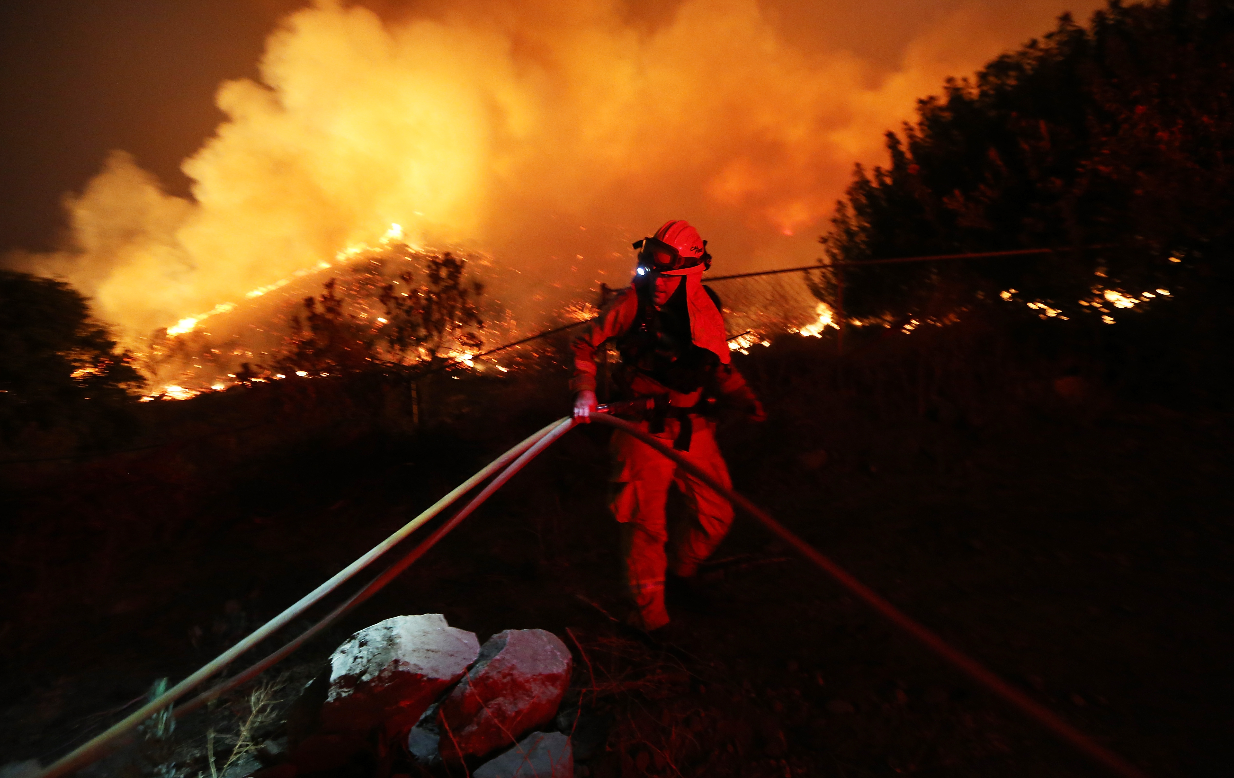 A firefighter works as the Holy Fire burns near homes on August 9, 2018 in Lake Elsinore, California. The fire continues to grow amidst a heat wave and has now burned 10,236 acres while remaining just five percent contained.