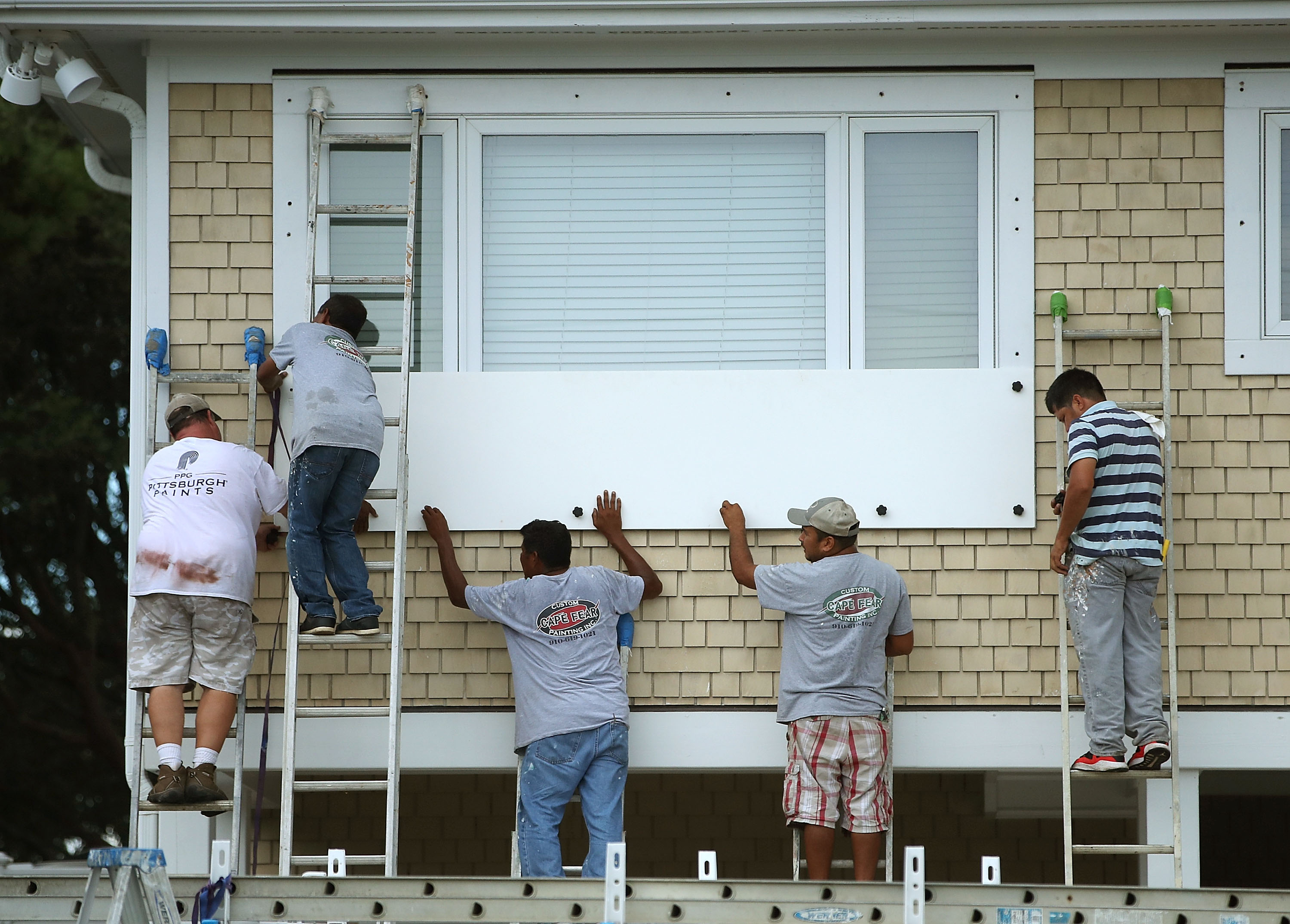 Workers board up a home while preparing for the arrival of Hurricane Florence on September 11, 2018 in Wrightsville Beach, United States. Hurricane Florence is expected on Friday possibly as a category 4 storm along the Virginia, North Carolina and South Carolina coastline.