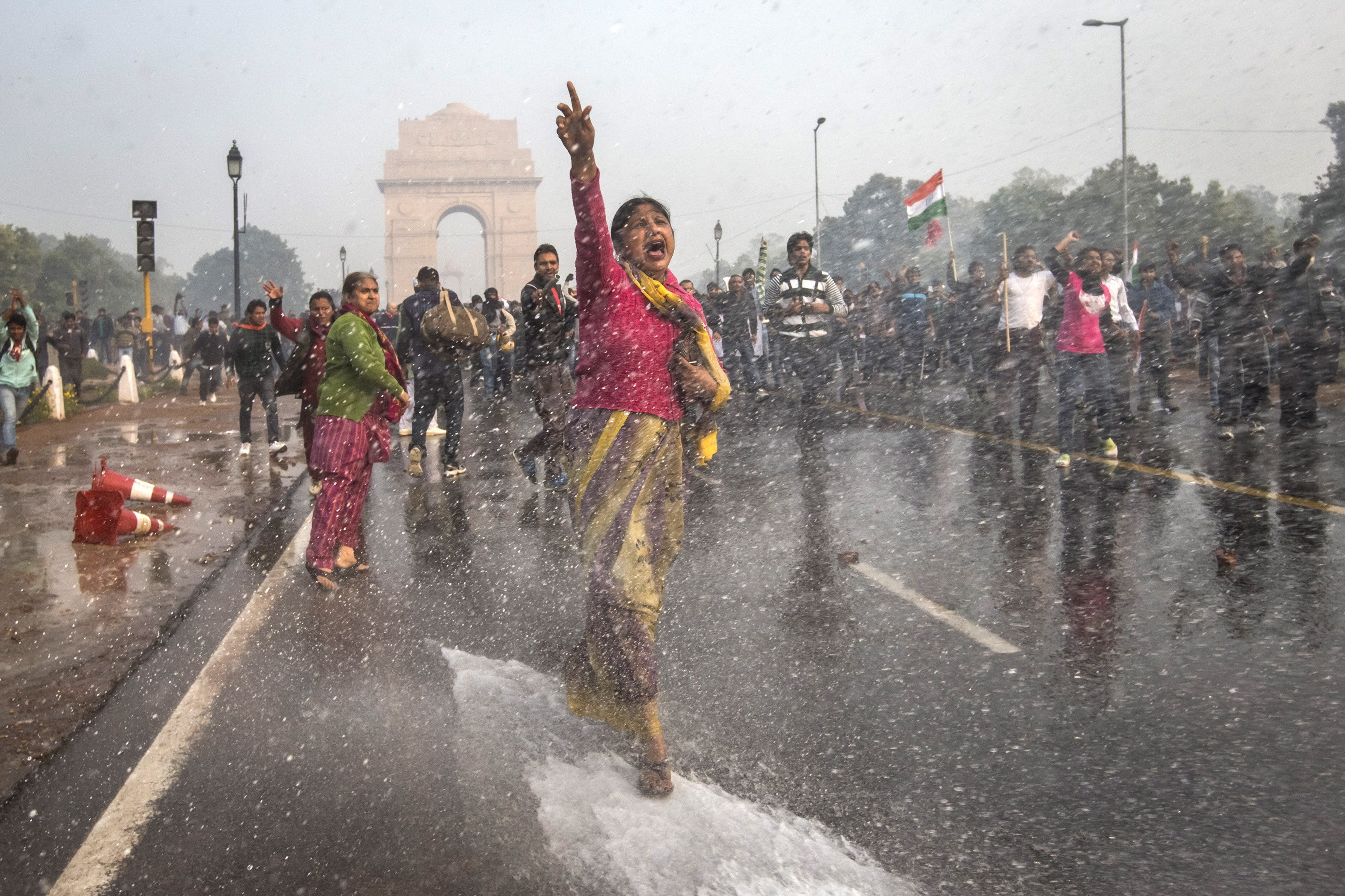 A protester chants slogans as she braces herself against the spray fired from police water canons during a protest against the Indian government's reaction to recent rape incidents in India, in front of India Gate on December 23, 2012, in New Delhi, India. (Getty)