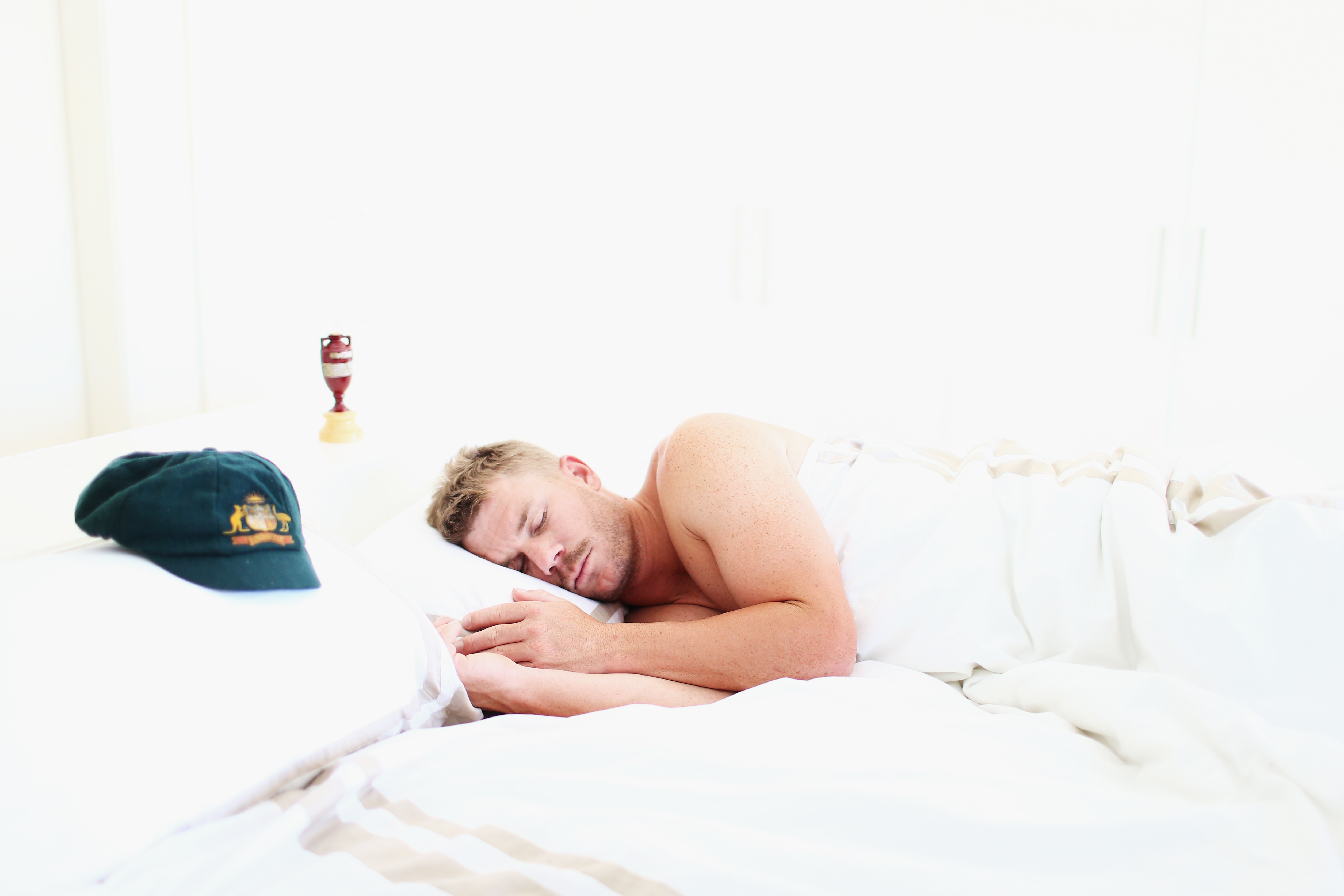 Australian Cricketer David Warner sleeps next to his Baggy Green Cap and a replica Ashes Urn at his home on January 6, 2014 in Sydney, Australia. Australia yesterday claimed a five-nil Ashes series victory over England in which Warner was leading run scorer.