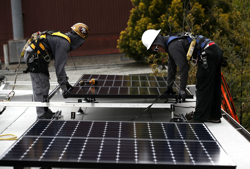 Workers install solar panels on the roof of a home on May 9, 2018, in San Francisco, California (Source: Getty Images)