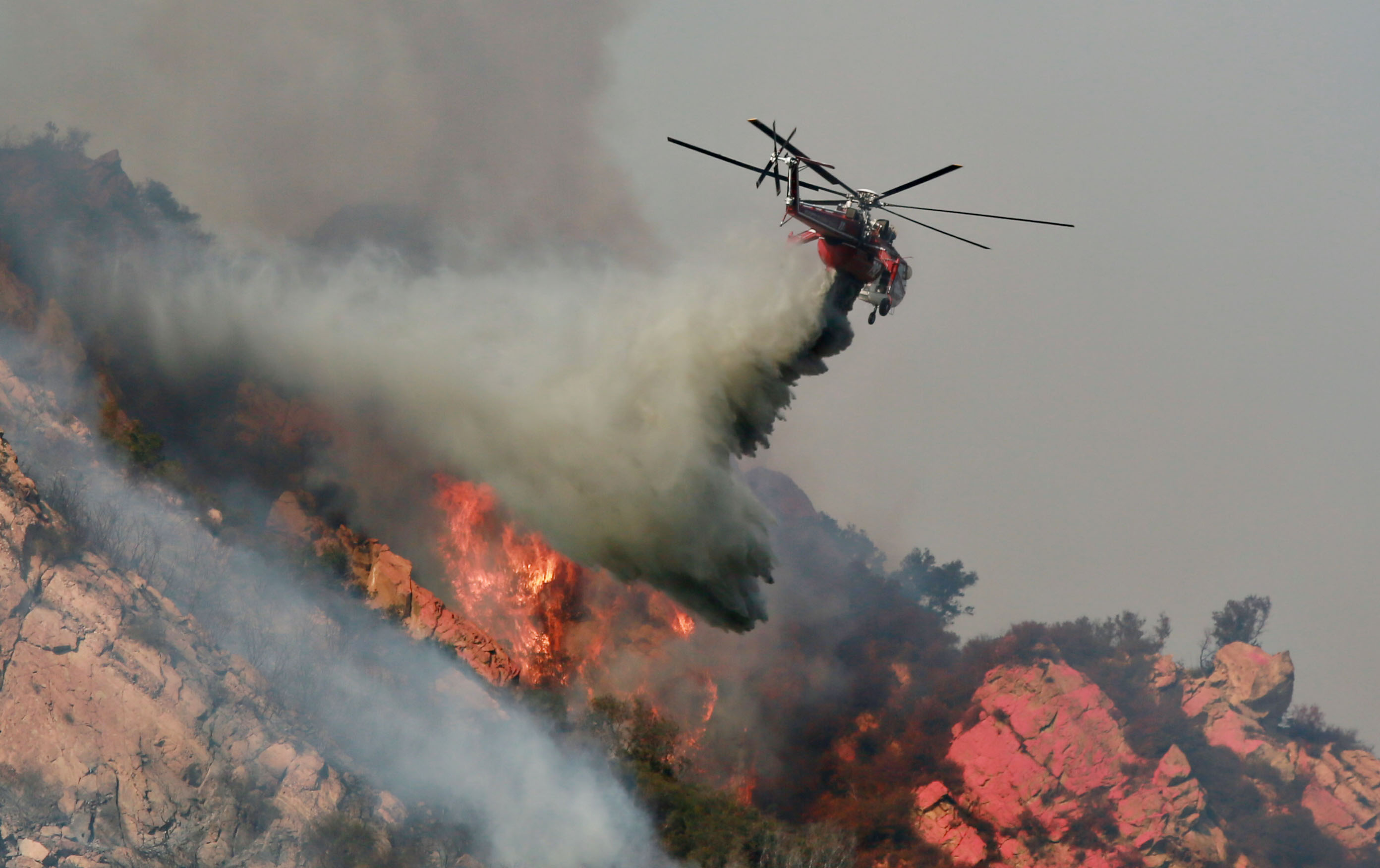 A helicopter drops flame retardant on a wildfire on November 10, 2018, in Malibu, California. (Getty Images)