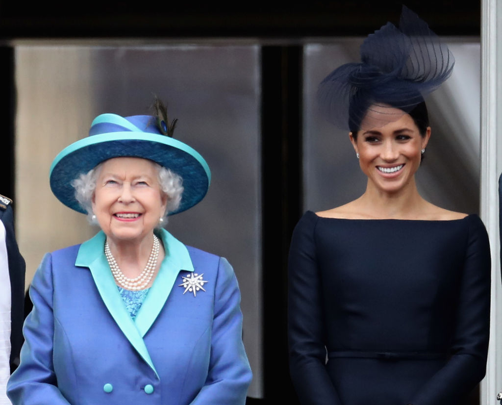 Queen Elizabeth II and Meghan, Duchess of Sussex watch the RAF flypast on the balcony of Buckingham Palace, as members of the Royal Family attend events to mark the centenary of the RAF on July 10, 2018 in London, England. (Photo by Chris Jackson/Getty Images)