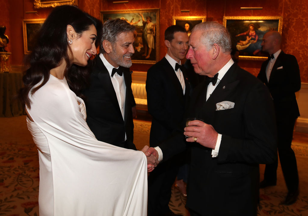 Amal Clooney and George Clooney speak to Prince Charles, Prince of Wales, as they attend a dinner to celebrate The Prince's Trust, hosted by Prince Charles at Buckingham Palace on March 12, 2019, in London, England. (Photo by Chris Jackson - WPA Pool/Getty Images)