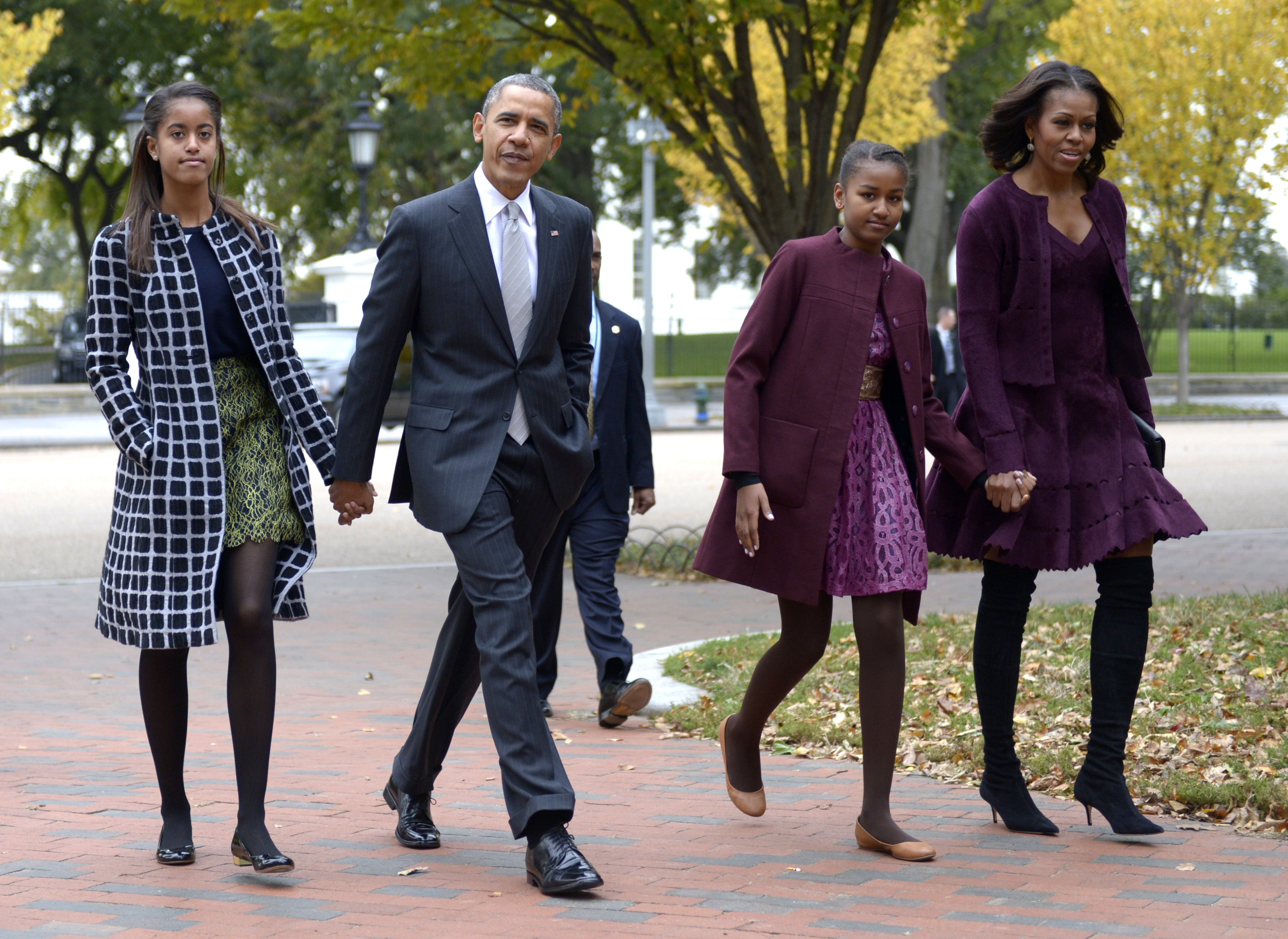 U.S. President Barack Obama walks with his wife Michelle Obama (R) and two daughters Malia Obama (L) and Sasha Obama (2R) through Lafayette Park to St John's Church to attend service October 27, 2013 in Washington, DC. Obama is scheduled to travel to Boston this week.