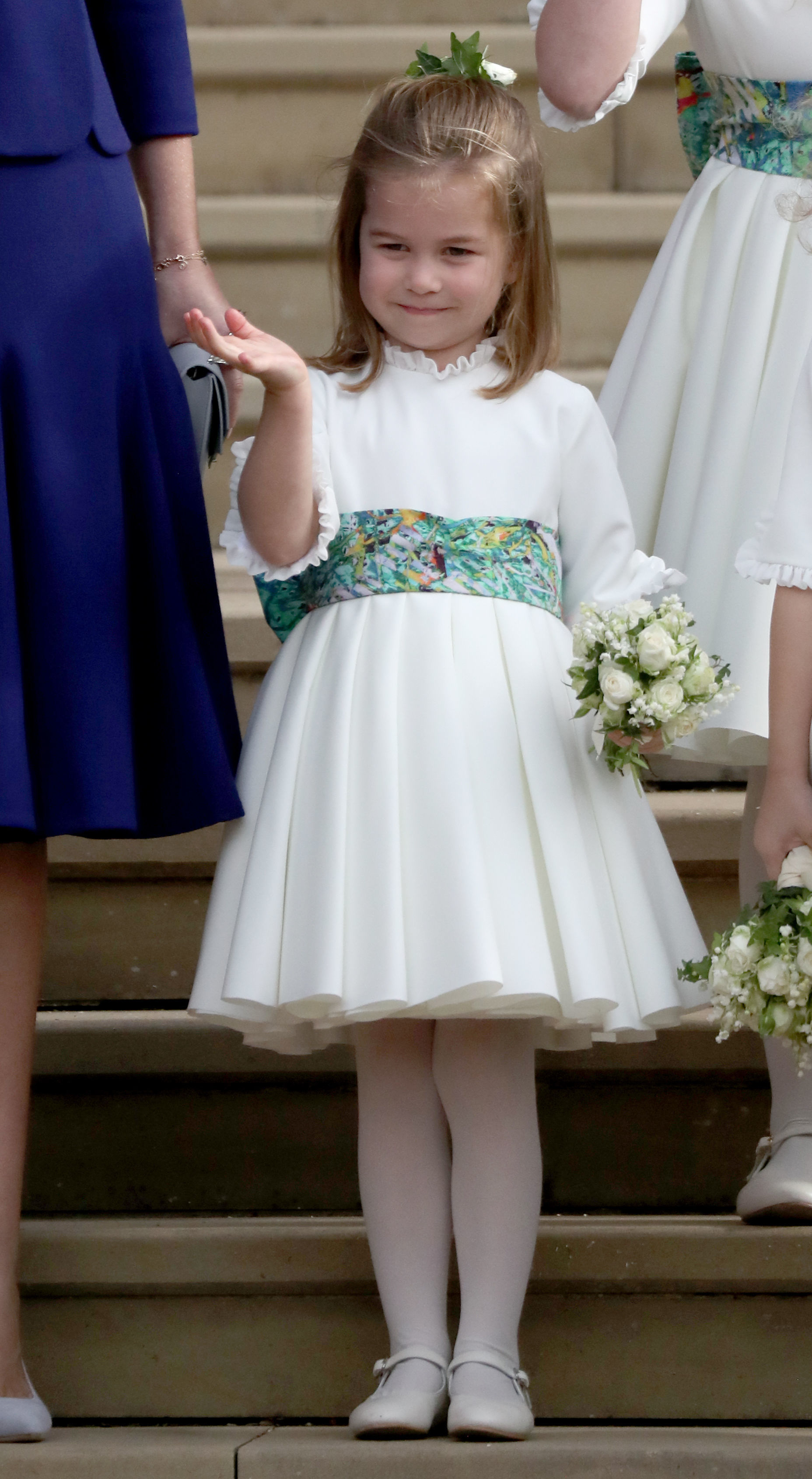 Bridesmaid Princess Charlotte of Cambridge waves as she stands on the steps after the wedding of Princess Eugenie of York and Jack Brooksbank at St. George's Chapel on October 12, 2018 in Windsor, England.