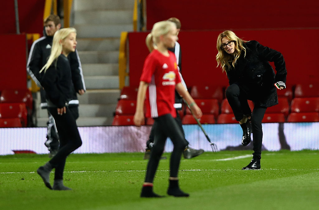 Actress Julia Roberts puts her shoe back on while watching her children play football after the Premier League match between Manchester United and West Ham United at Old Trafford on November 27, 2016, in Manchester, England. (Photo by Clive Brunskill/Getty Images)
