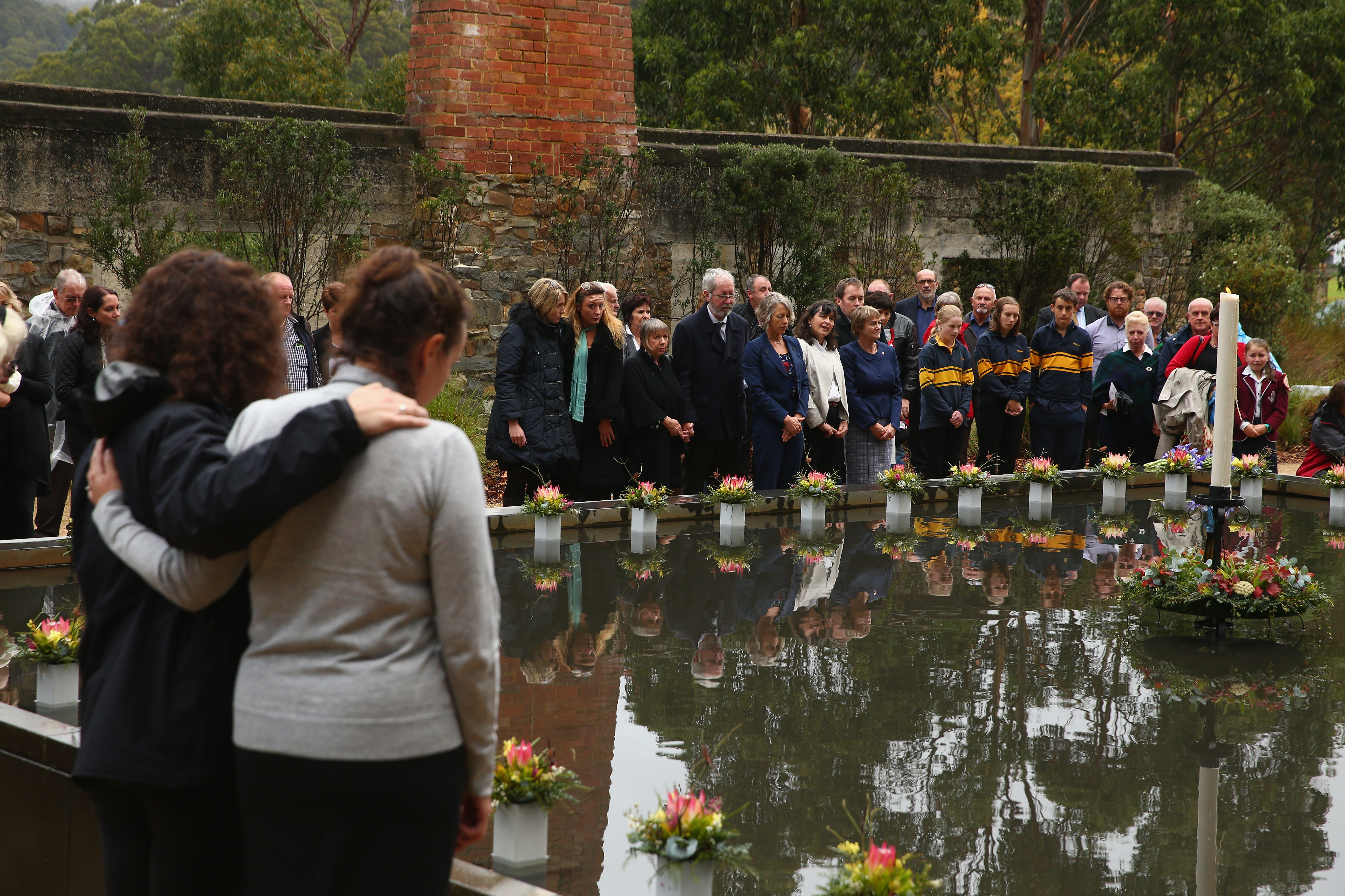 Family and community members lay 35 floral tributes in the Memorial Pool to remember the victims during the 20th anniversary commemoration service of the Port Arthur massacre on April 28, 2016, in Port Arthur, Australia. The historic town became infamous on April 28, 1996, when Martin Bryant began shooting indiscriminately with a high-powered rifle on people visiting the site. 35 people were killed and a further 23 were injured in what remains the world's worst massacre by a lone gunman. The tragedy transformed gun legislation in Australia, with then- Prime Minister John Howard introducing the National Firearms Agreement, banning all semi-automatic rifles and all semi-automatic and pump-action shotguns and introducing stricter licensing and ownership controls. (Source: Robert Cianflone/Getty Images)