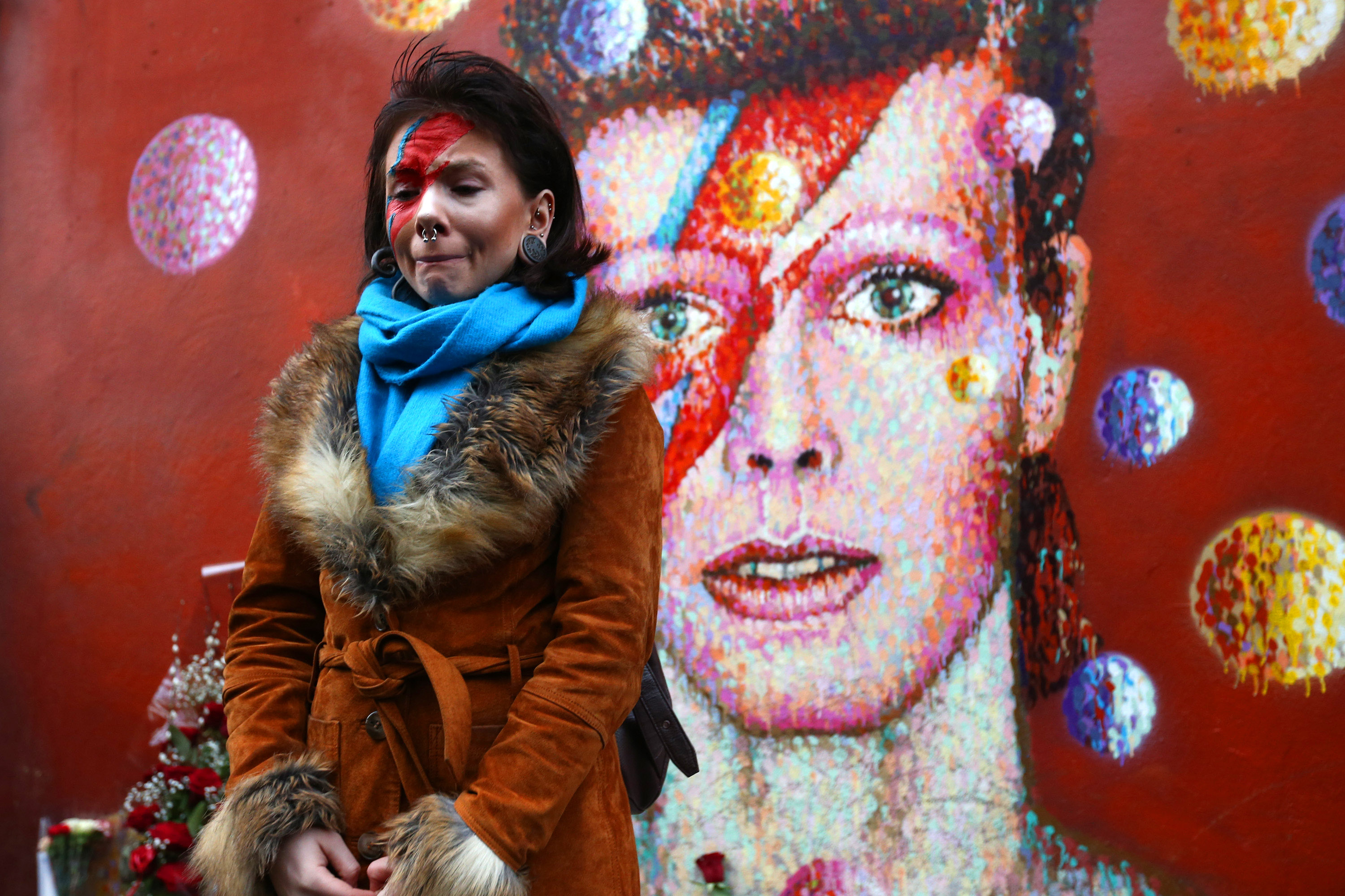 David Bowie fan Rosie Lowery pauses after laying flowers at his mural in Brixton on January 11, 2016 in London, England. British music and fashion icon David Bowie died earlier today at the age of 69 after a battle with cancer. Source: Getty