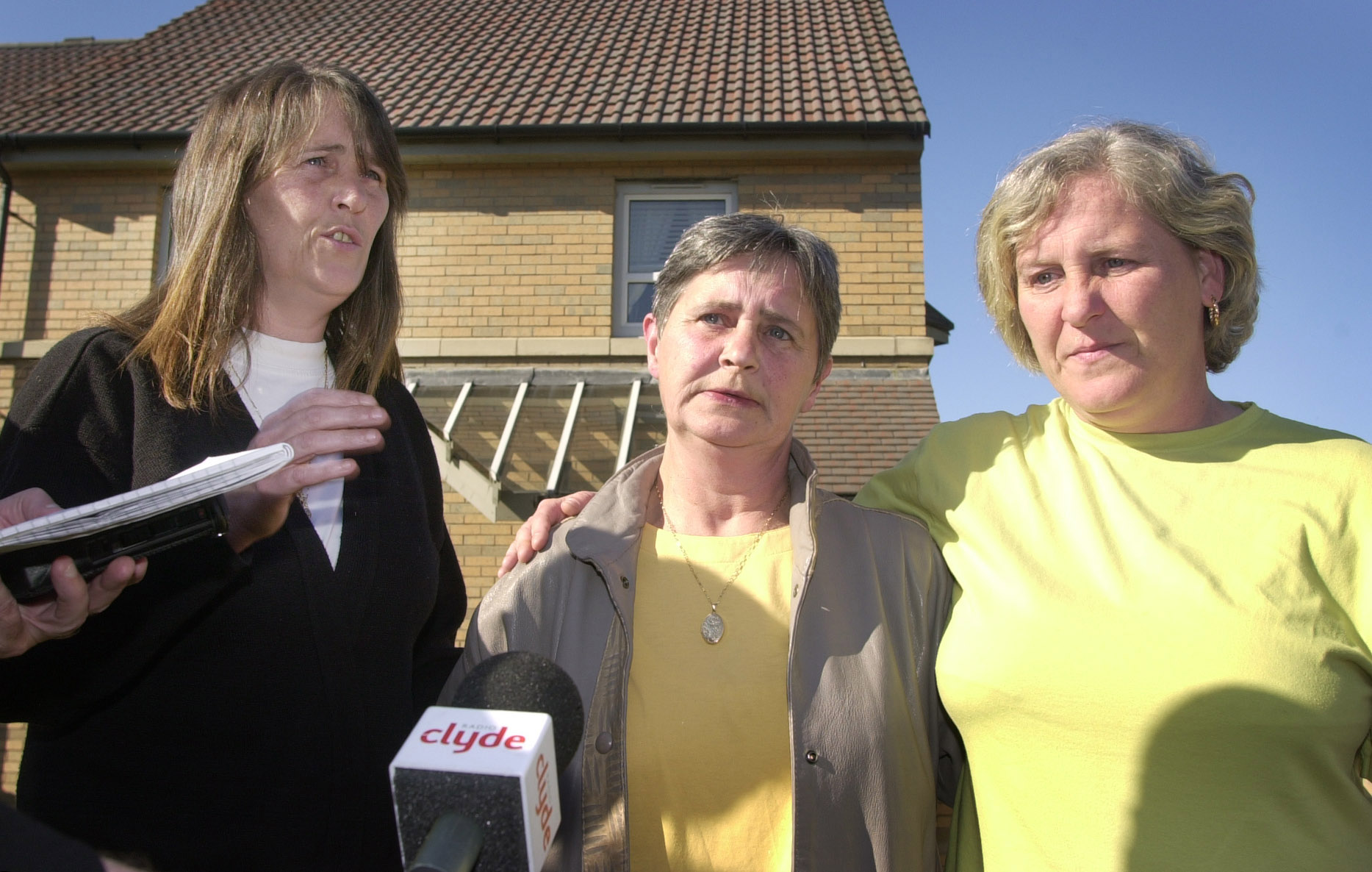 Mother Catherine Gallacher, 58, (centre) accompanied by daughter's Yvonne, (right) and Catherine, from her front garden in Glasgow, gives her reaction to the verdict delivered upon Angus Sinclair, 56, who was found guilty at Glasgow High Court (Source: Ben Curtis - PA Images/PA Images via Getty Images)