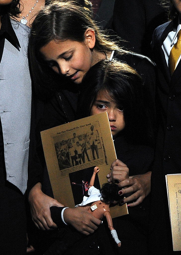 Michael Jackson's daughter Paris Jackson (top) holds her brother Prince Michael Jackson II (also known as Blanket) at the Michael Jackson public memorial service held at Staples Center on July 7, 2009 in Los Angeles, California. (Photo by Gabriel Bouys-Pool/Getty Images)