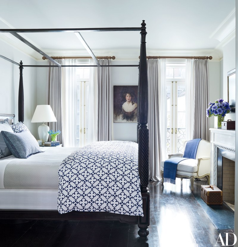 In the master bedroom, an Anglo-Indian tester bed is dressed in John Robshaw block-printed linens. The oil portrait is Edwardian and was purchased in London; a throw from the Silver Peacock drapes the 19th-century armchair.