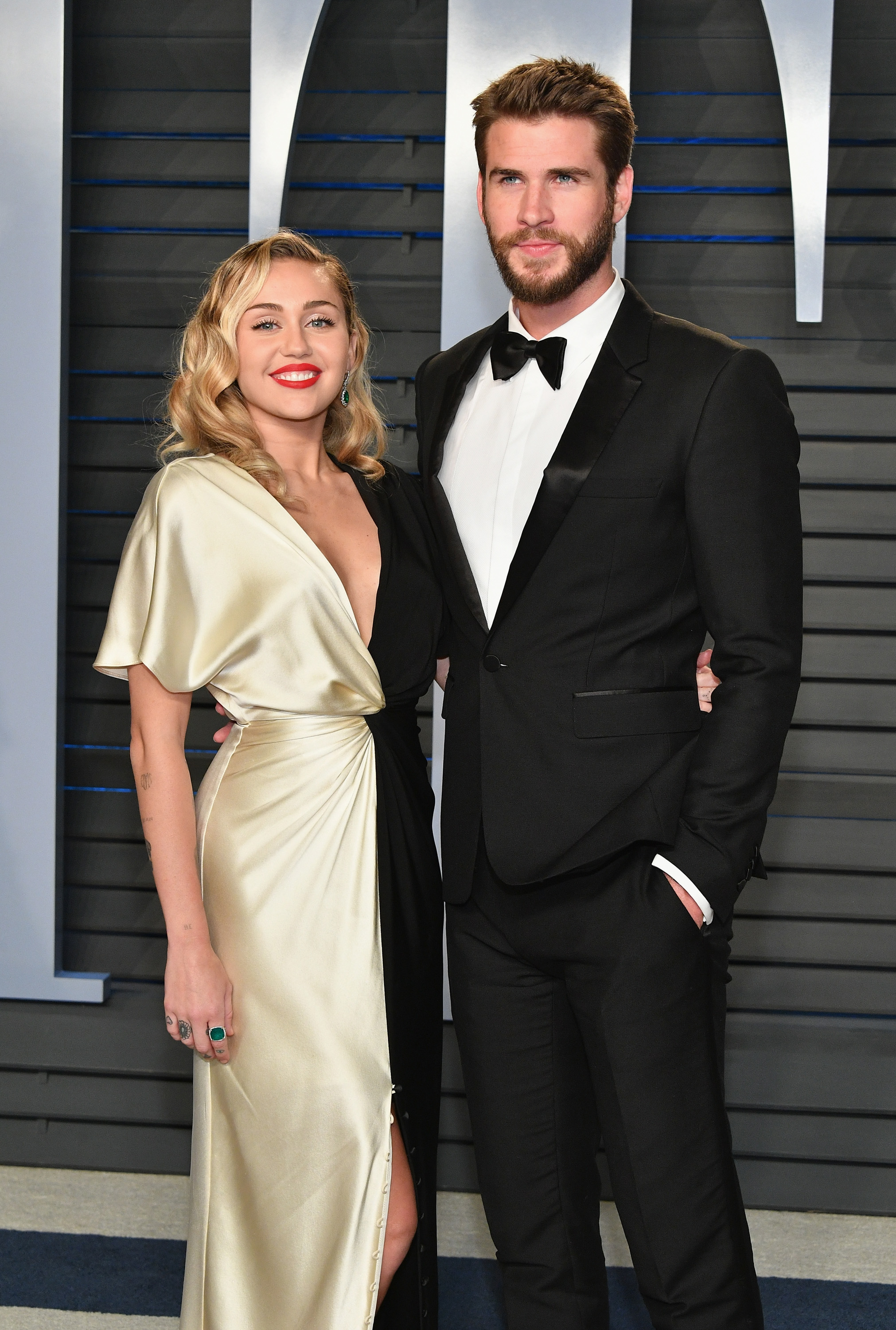 Miley Cyrus (L) and Liam Hemsworth attend the 2018 Vanity Fair Oscar Party hosted by Radhika Jones at Wallis Annenberg Center for the Performing Arts on March 4, 2018 in Beverly Hills, California.