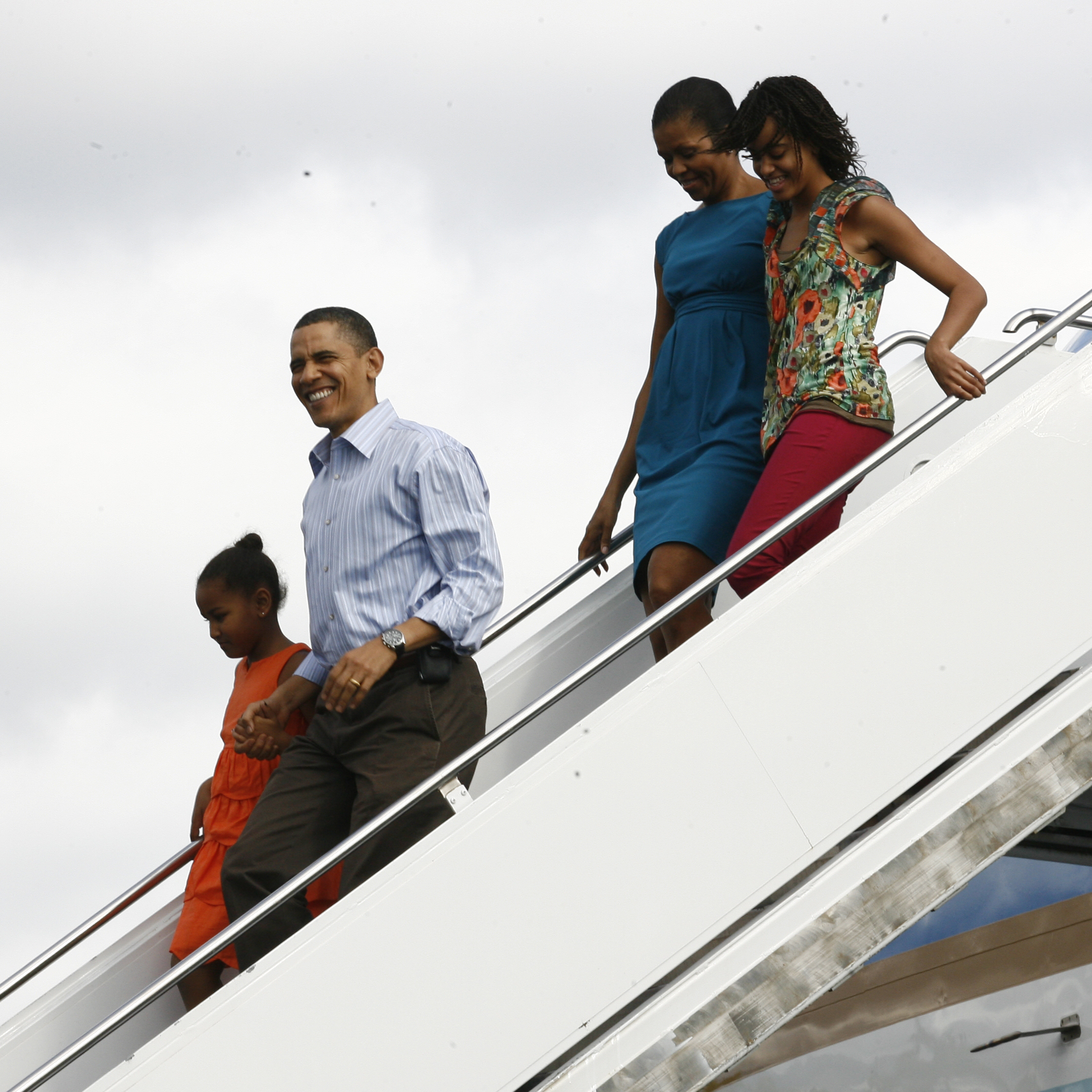 U.S. President Barack Obama, first lady Michelle Obama and their children Sasha and Malia disemark from Air Force One at Hickam Air Force Base on December 24, 2009 in Honolulu, Hawaii.