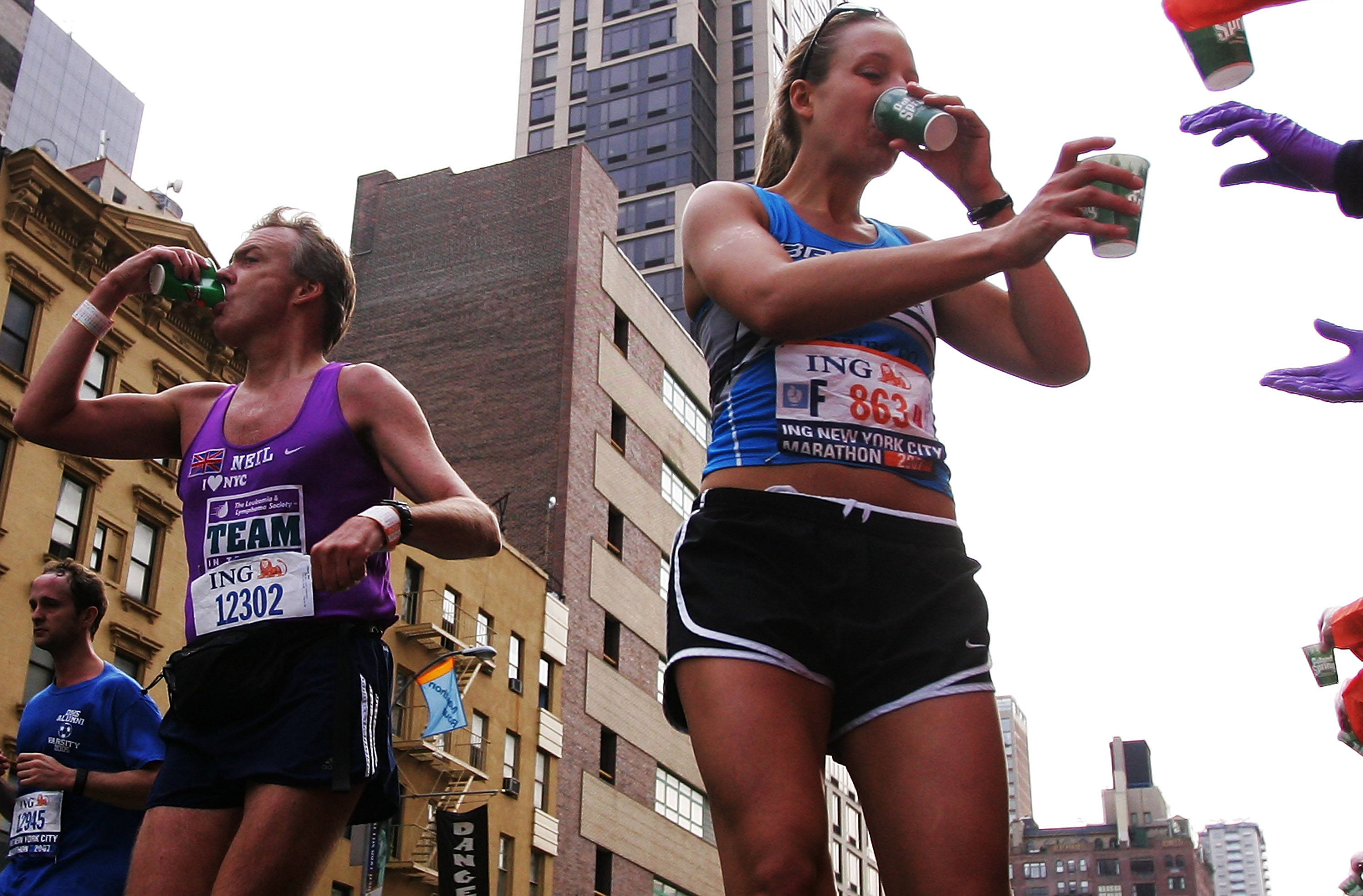 Competitors grab water from a drink station as they run down First Avenue during the 2007 New York City Marathon on November 4, 2007 in New York City.