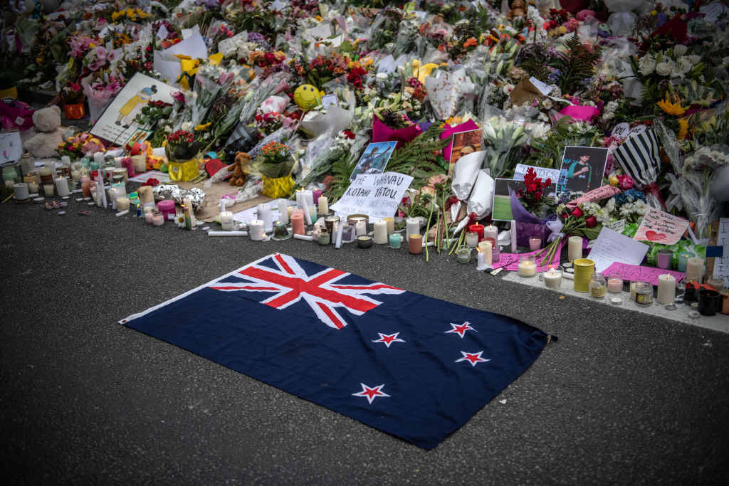 A New Zealand flag is placed next to flowers and tributes near Al Noor mosque on March 18, 2019 in Christchurch, New Zealand. 50 people were killed, and dozens are still injured in hospital after a gunman opened fire on two Christchurch mosques on Friday, 15 March (Getty Images)